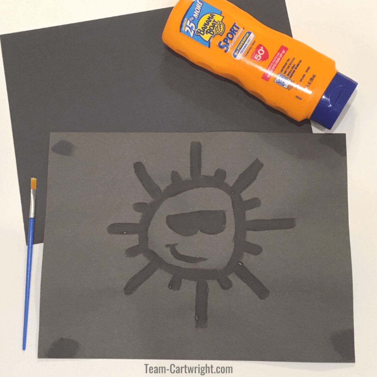 2 sheets of black paper. one has a sun with sunglasses and a smiley face painted on it with suncream. The bottle of suncream is above and a paintbrush to the left