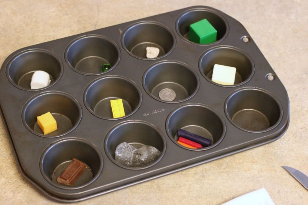 a muffin tray is filled with different items including chocolate, sweets, metal and wax crayons