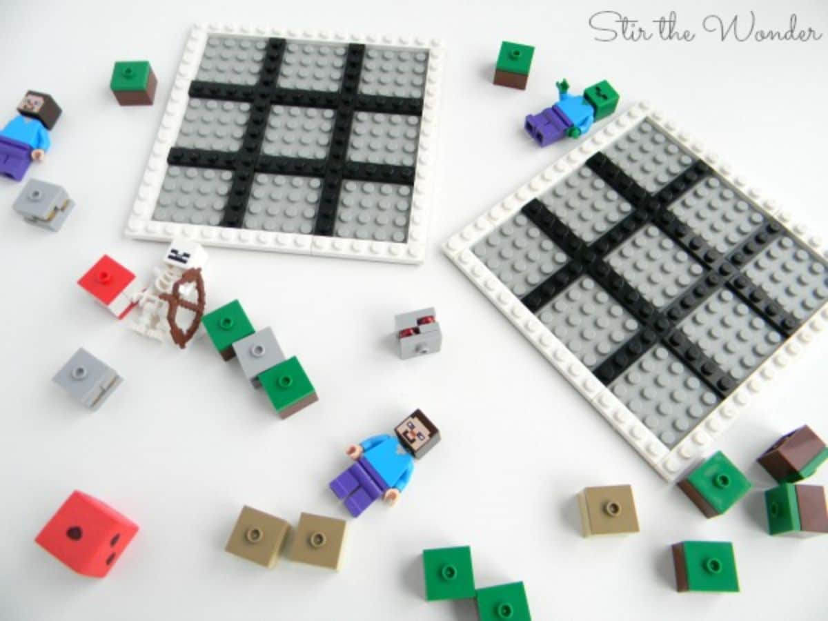 on a white table are 2 grey and black grids made out of lego. Scattered arounf are three minecraft figures and some minecraft lego bricks