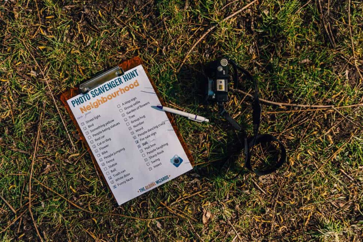 On a patch of grass is a scavenger hunt sheet on a clipboard with a pen and a camera with a strap next to it