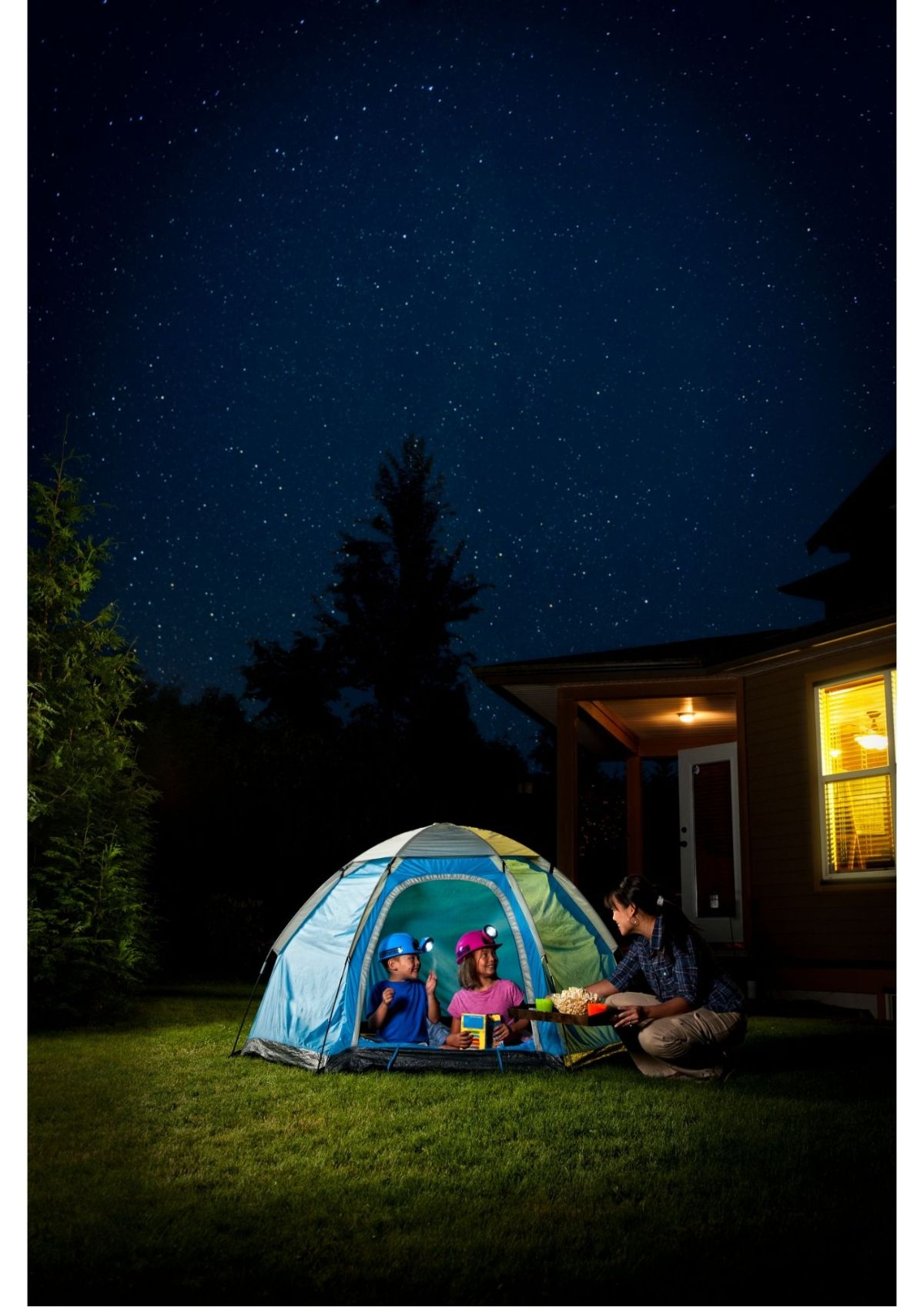 under a night sky, 2 children sit in a pop up tent pitched in their backgarden. Their mom is bringing them food on a tray