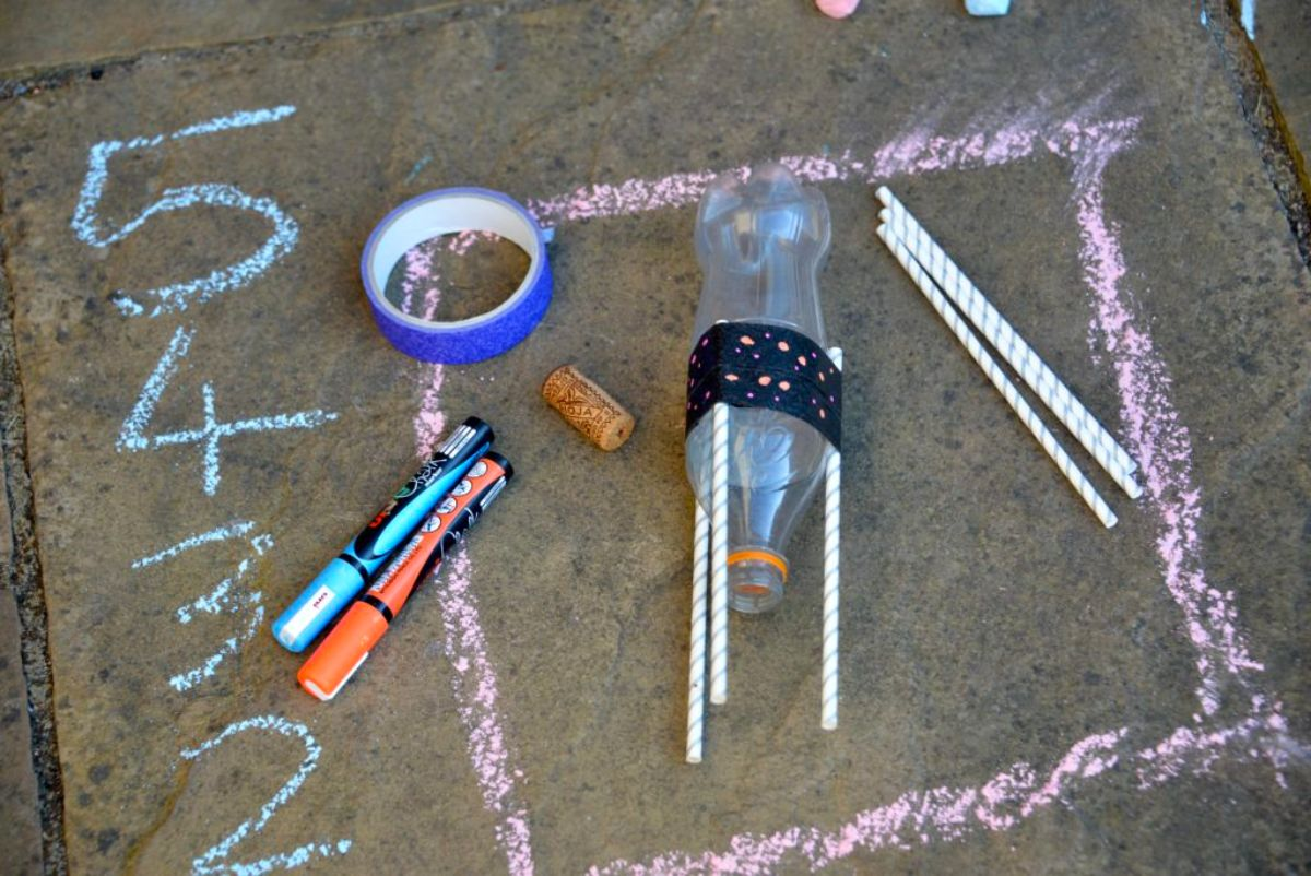 a square is chalked on pavement with the numbers 5 to 1 on the side. Also in the frame is a plastic soda bottle, marker pens ,tape, a cork and some straws