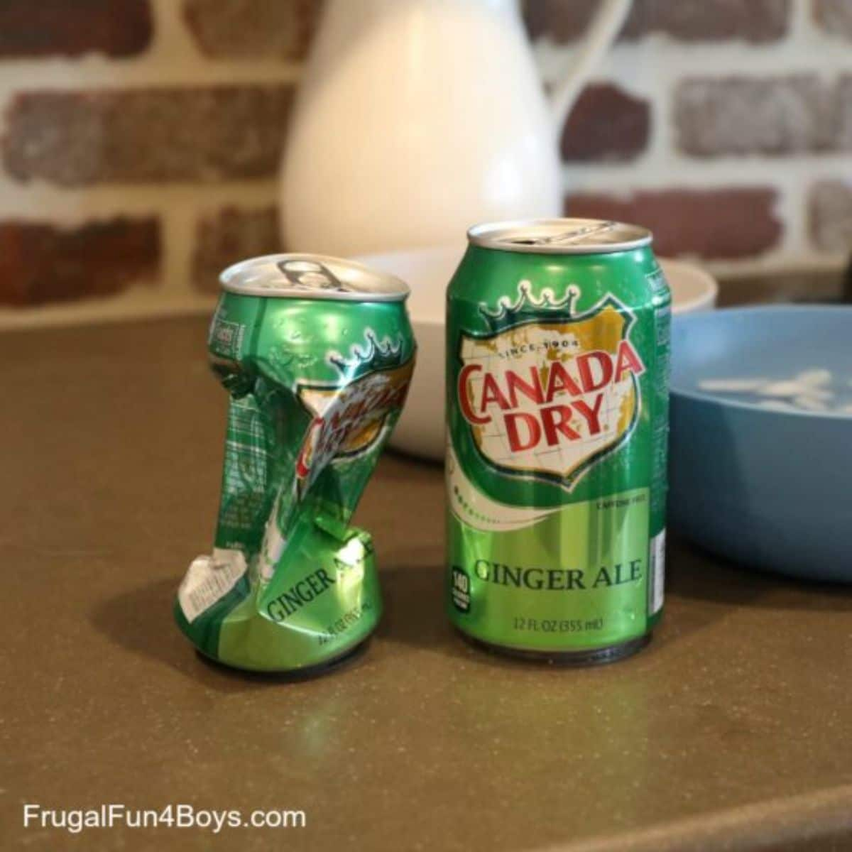 2 Canada Dry cans are on a kitchen counter, one crushed. one white and one blue bowl sits behind