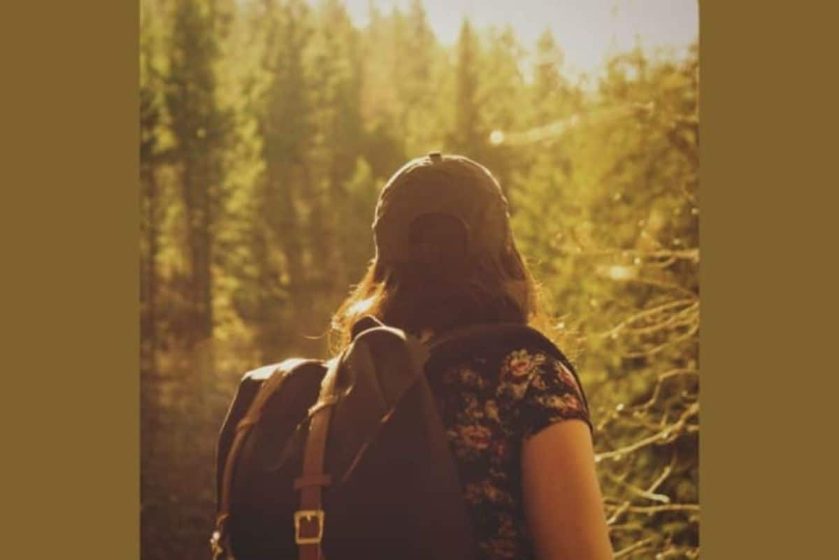 a woman walks away from the camera into a forest