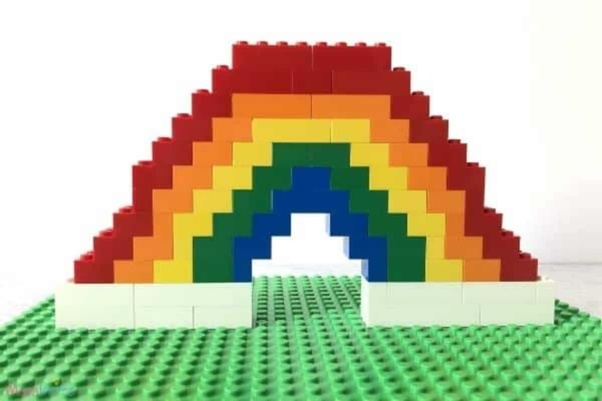 A rainbow made out of lego sitting on a green board