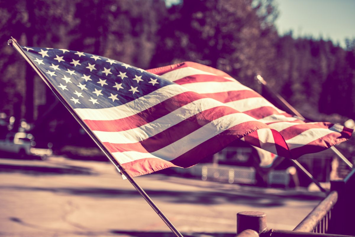 Against a bacground of a town is an America flag blowing in the breeze