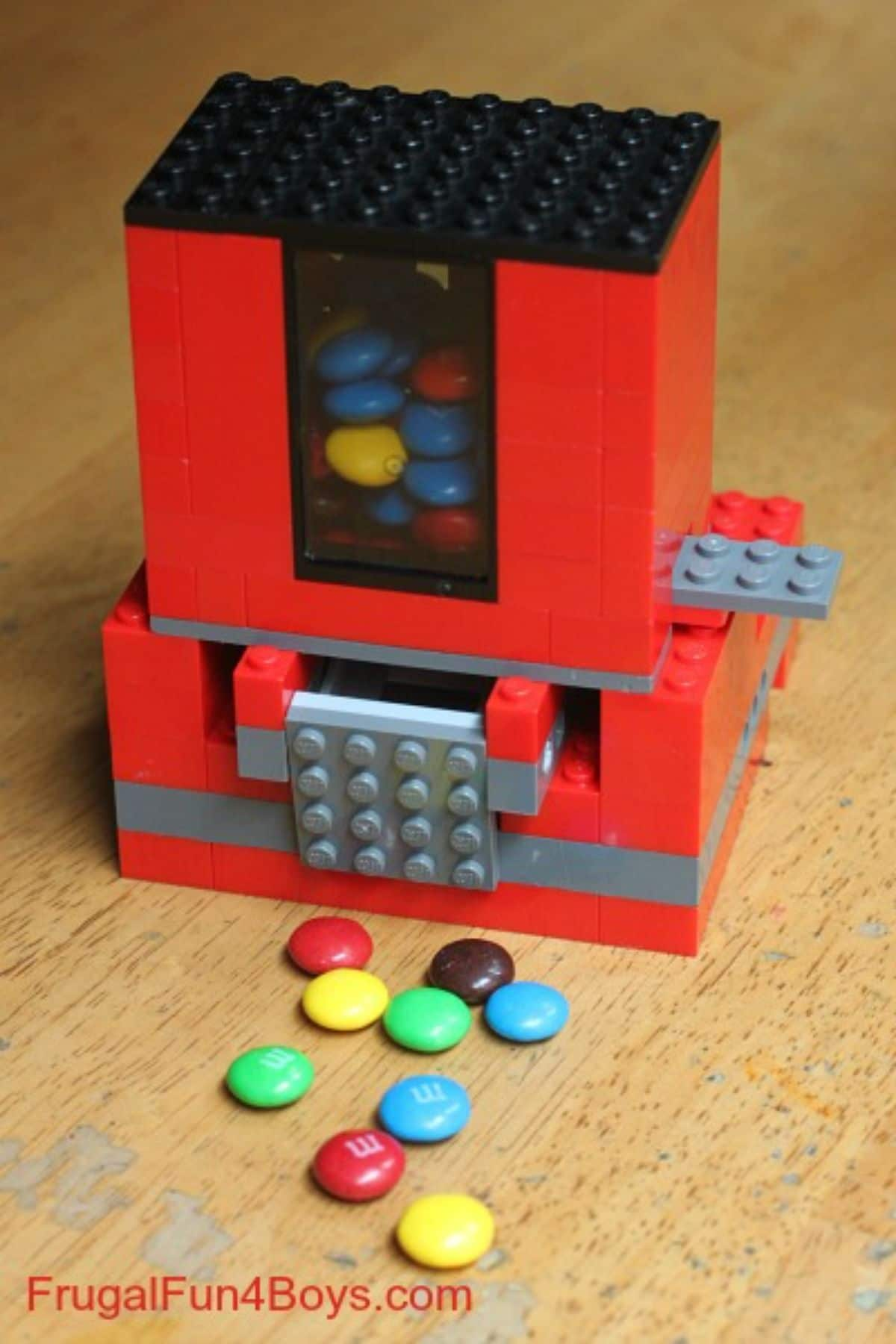 a candy dispenser is made out of lego. candy sweets are in front of it