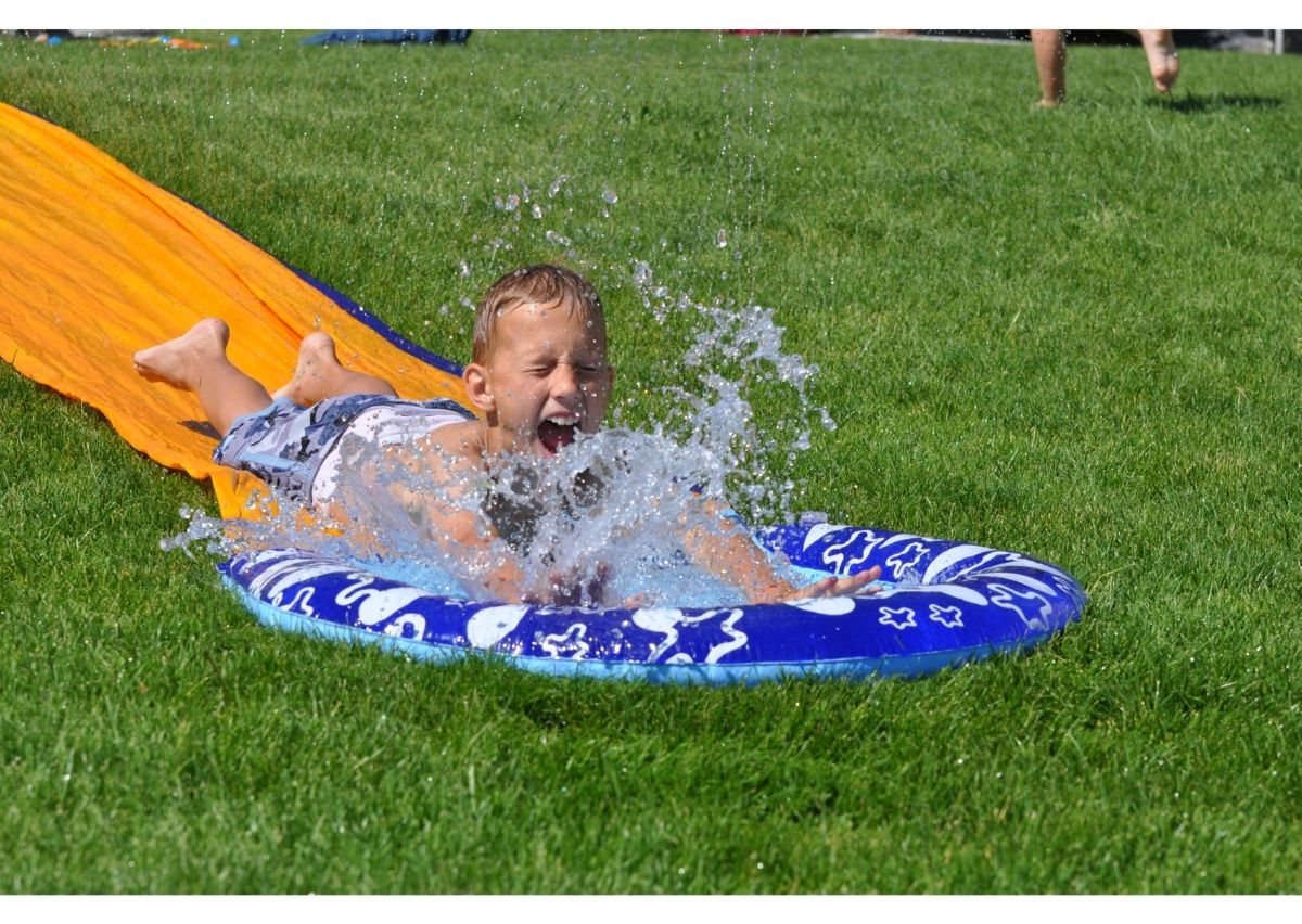 a child is sliding down the slip n slide, into a pool of water splashing up around him