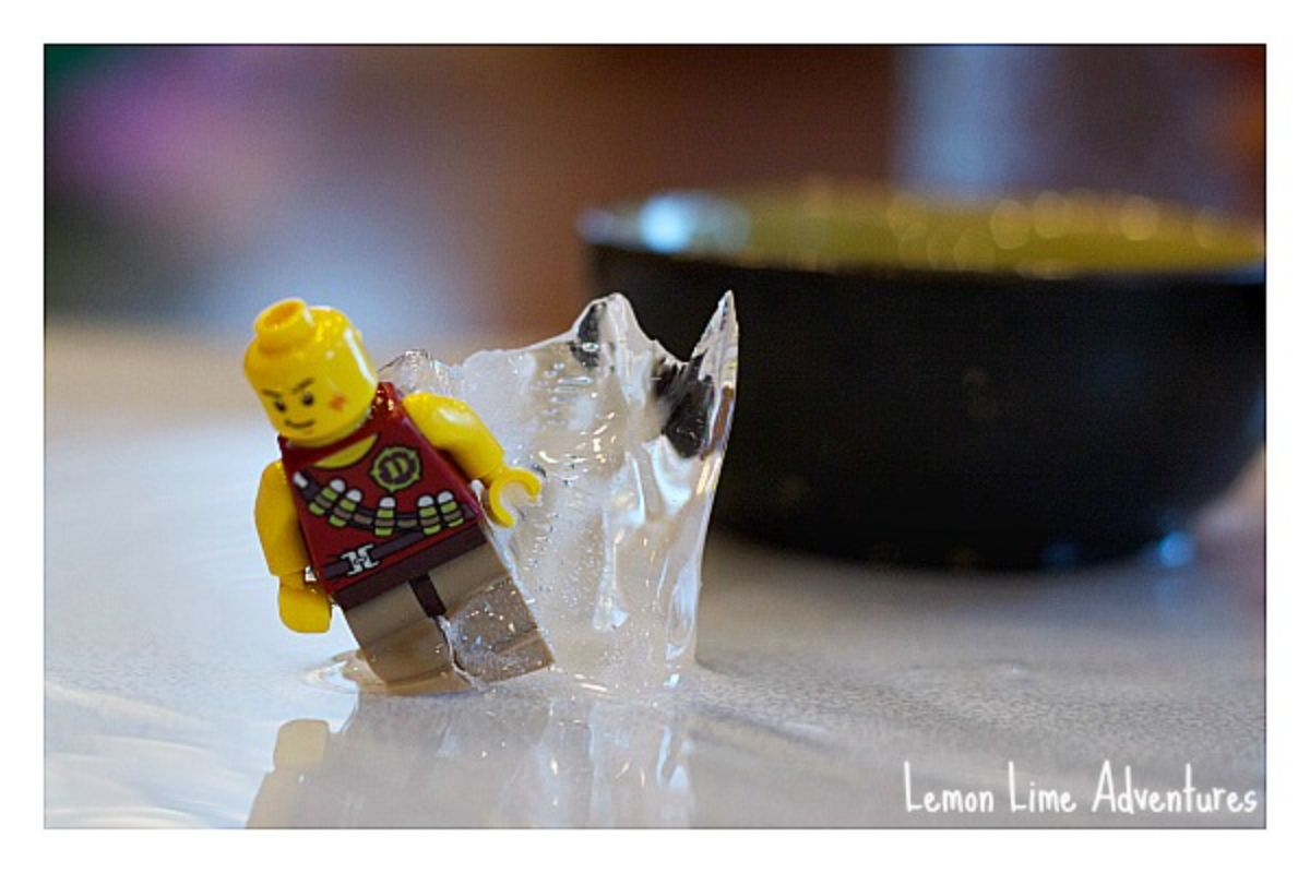 a lego figure sticks out of a block of ice with a black bowl behind it