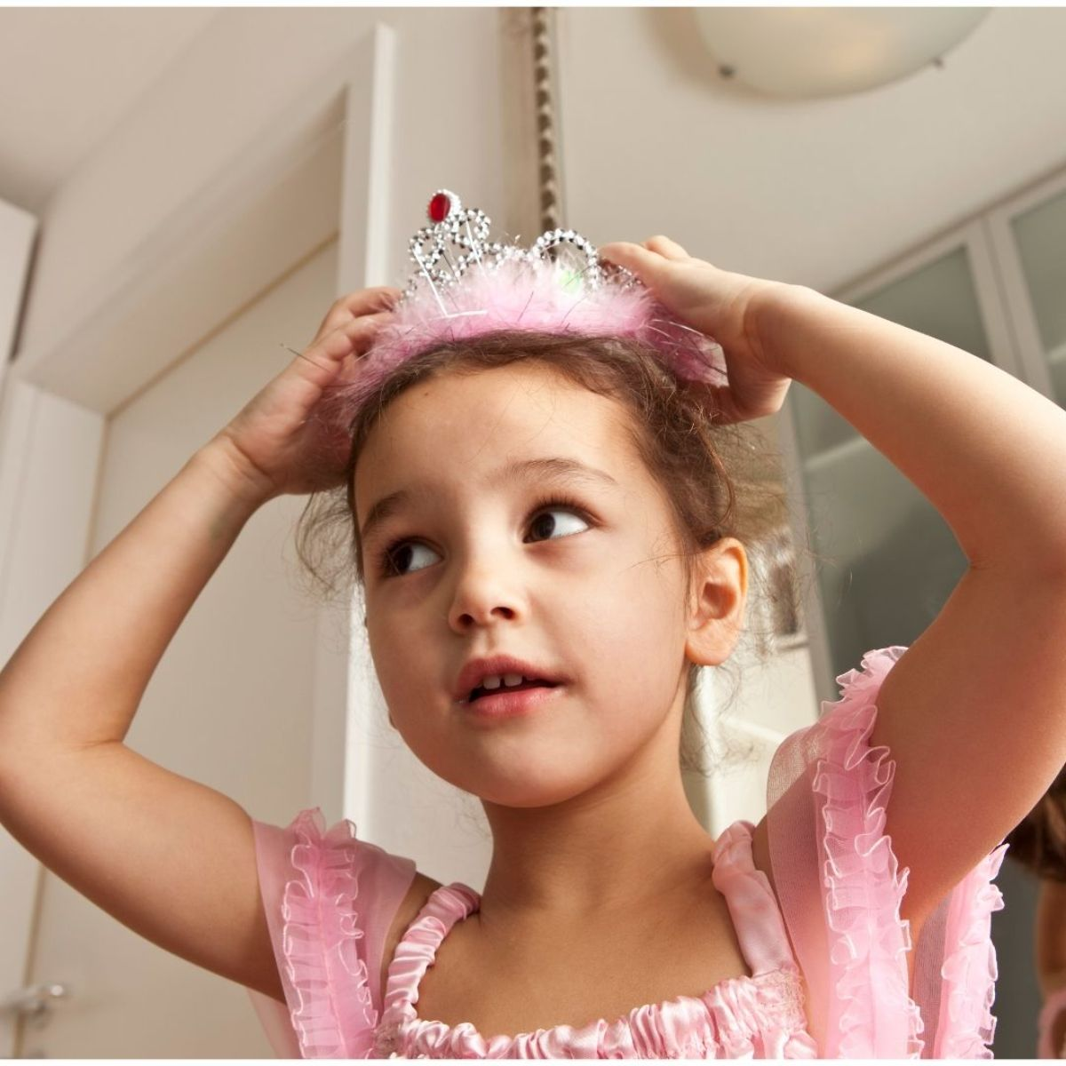 a girl in a pink dress is placing a tiara on her head