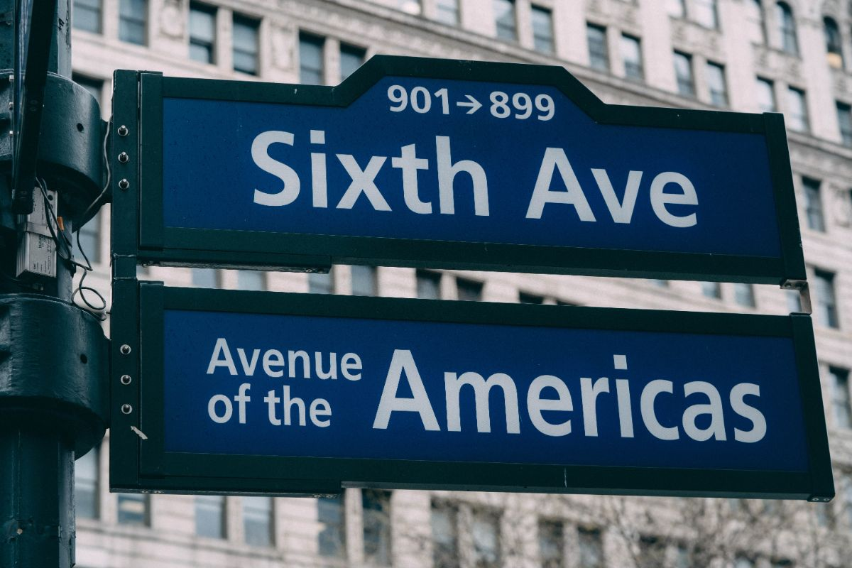 ROad signs for Sixth Avenue and Avenue of the Americas against a street background