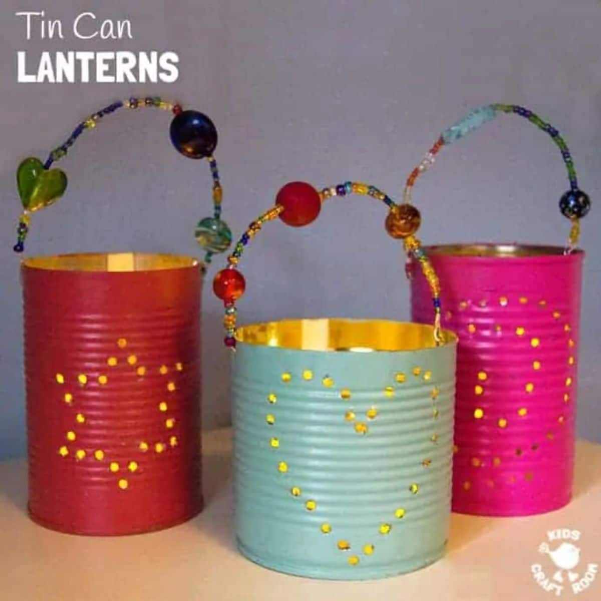 """The text reads """"Tin Can Lanterns"""" The image is of 3 tin cans, painted red, turquoise and pink. Hoeles are punched in the cans and beaded handles are attached to the rims"""