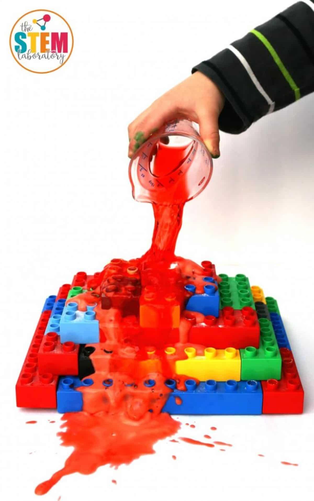 a hand pours red liquid onto a pyramid made of lego