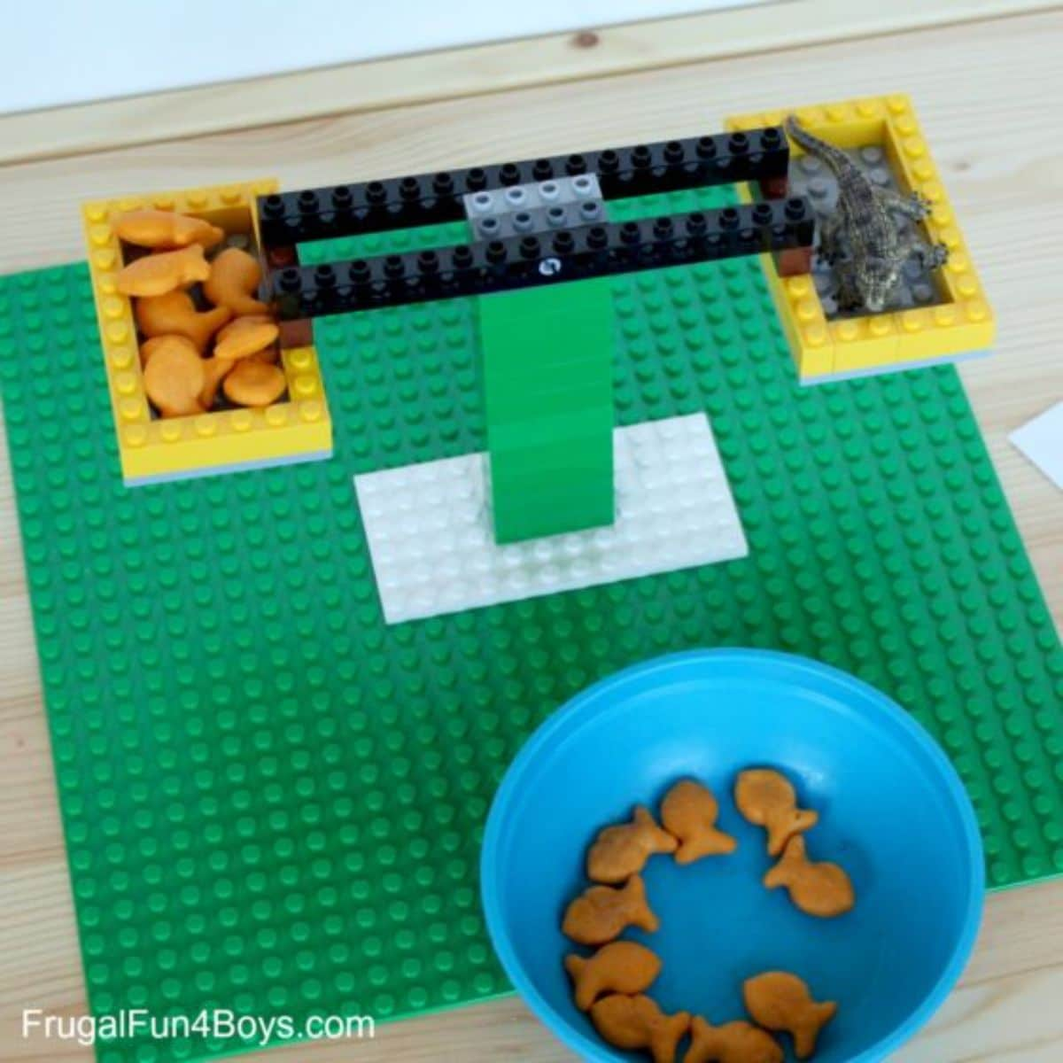 a set of scales made out of lego with 2 baskets filled with goldfish crackers, and a crocodile. In front is a blue bowl full of goldfish crackers