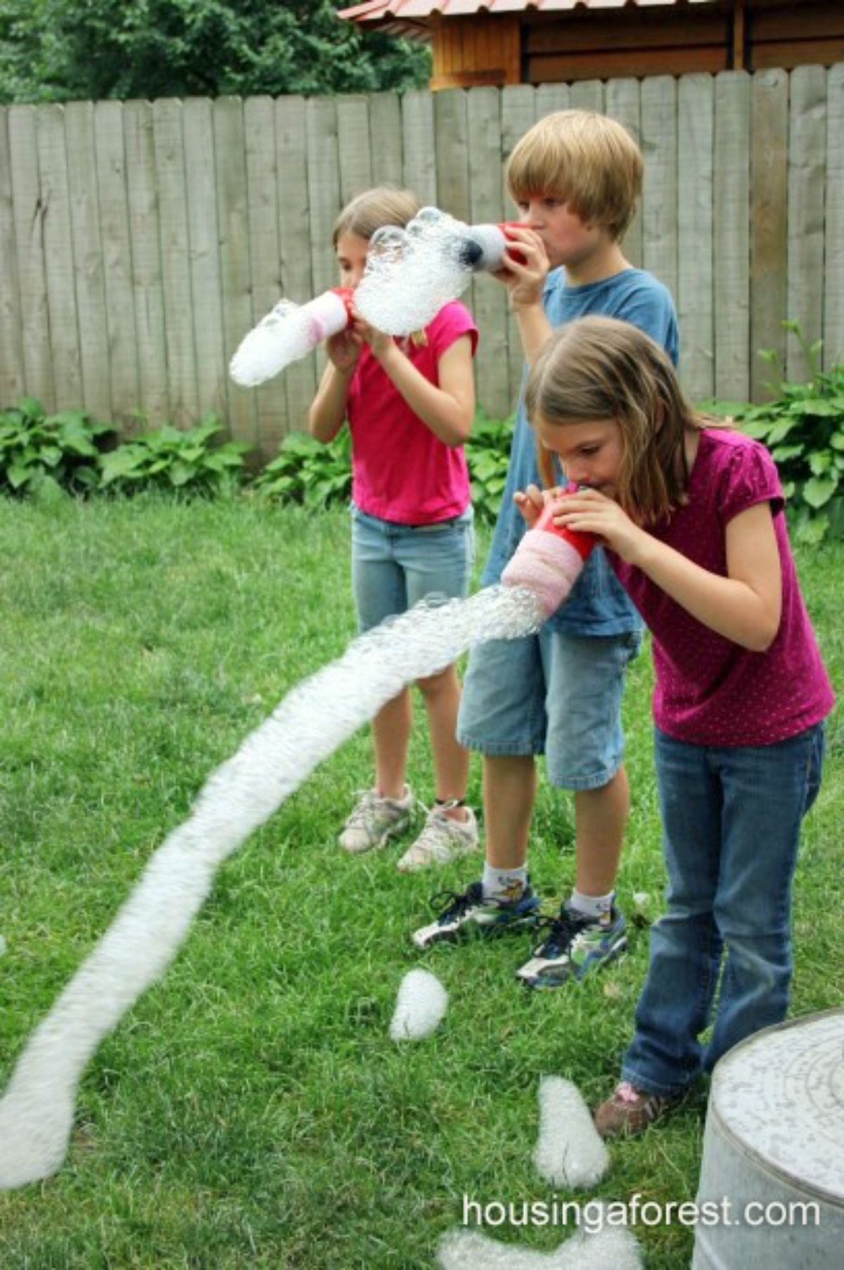 in a garden are 3 children holding plastic bottles to their mouths and blowing bubbles out of them