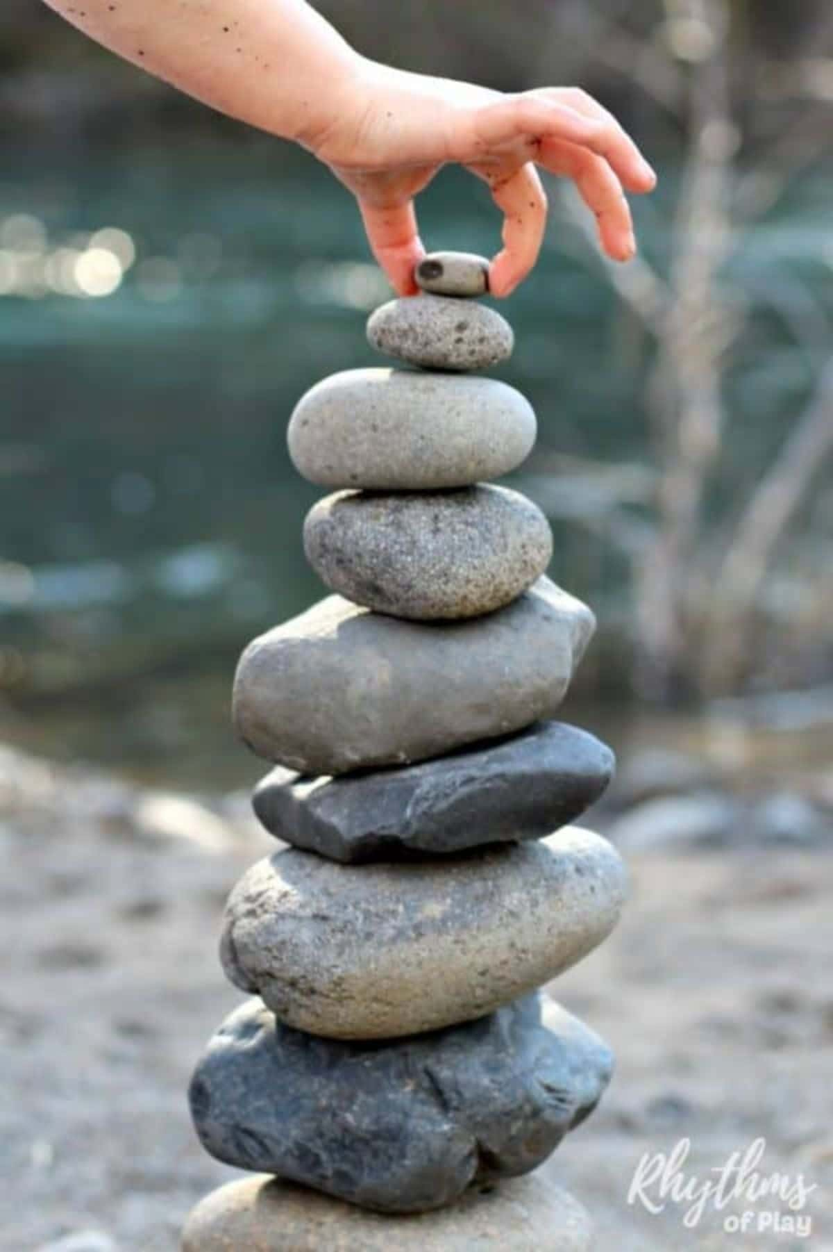 a hand places a small pebble on the top of a towering pile of stones.