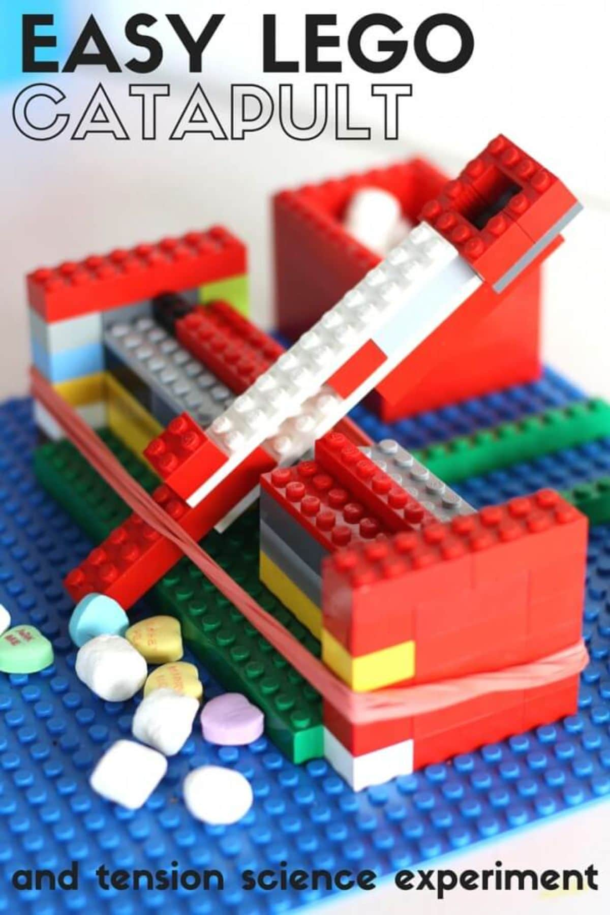 """The text reads """"Easy LEGO catapult and tension science experiment"""" The image is of a catapult made of lego with sweets at the front"""