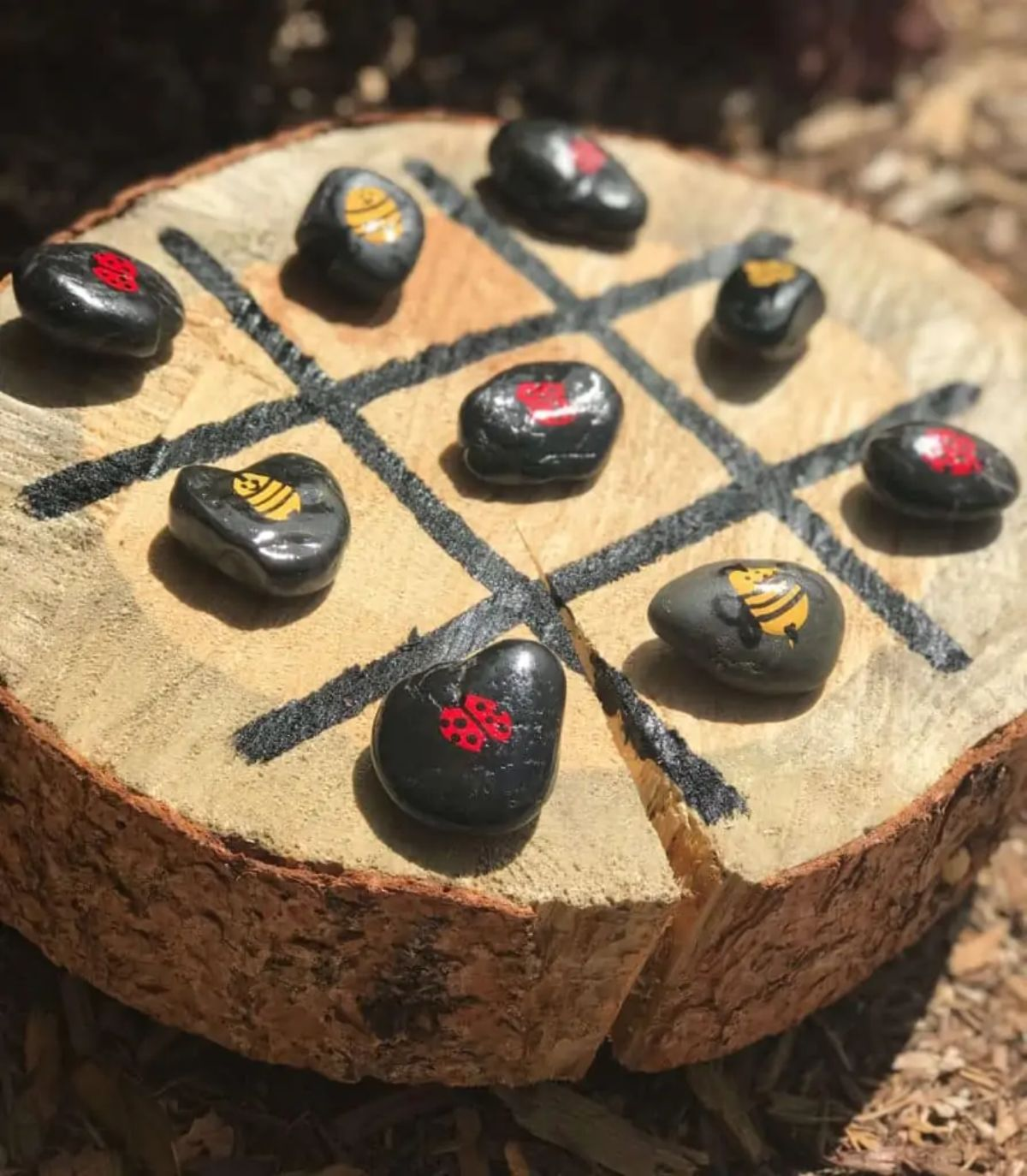 A log slice sits on some dirt, with a tic tac toe board painted on it. 9 painted stones sit in the squares