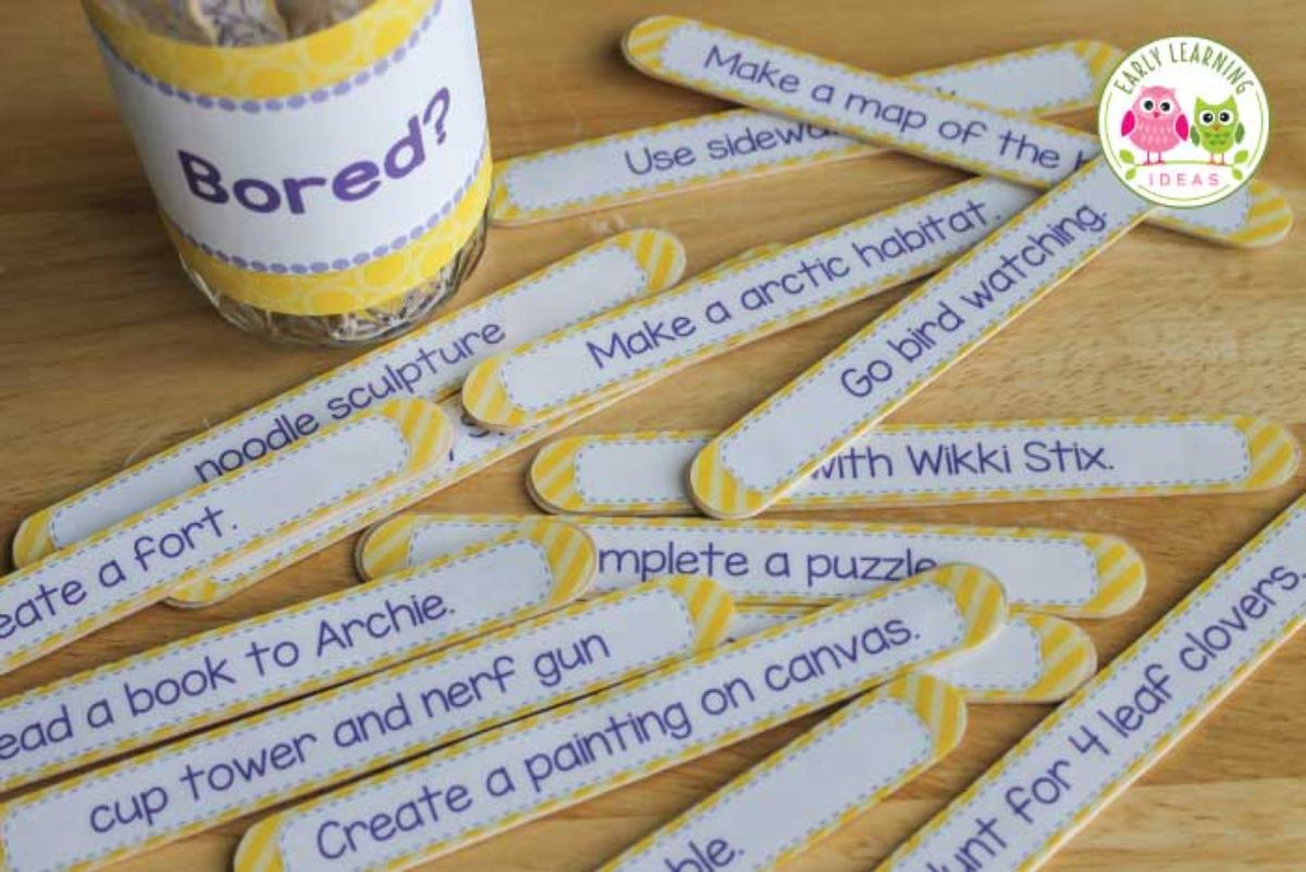 """on a table are lollysticks colored yellow with activities printed on them. Behind them is a glass jar labelled with """"Bored?"""""""