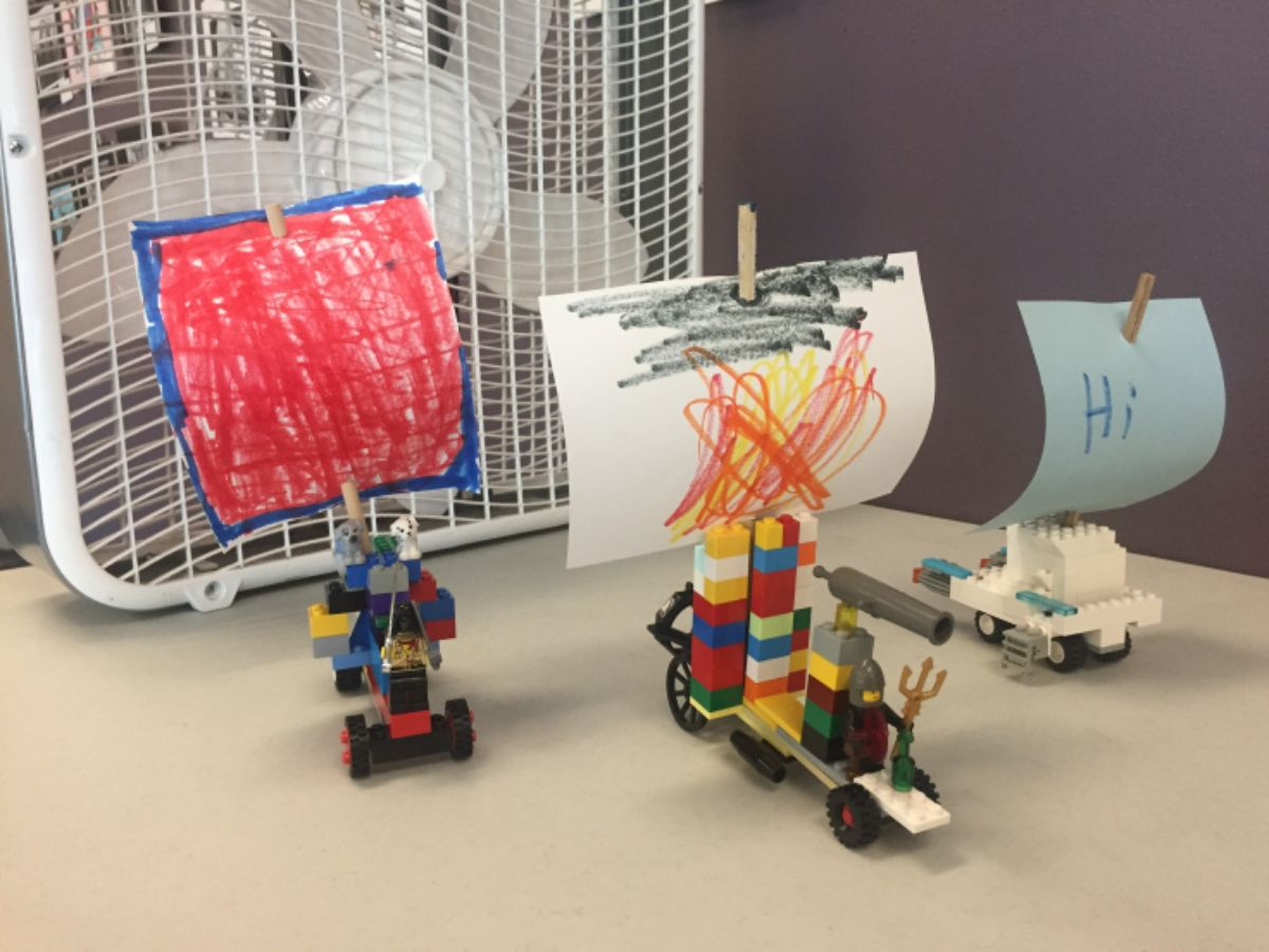 in front of a fan are 3 vehicles made of lego on wheels, with paper sails