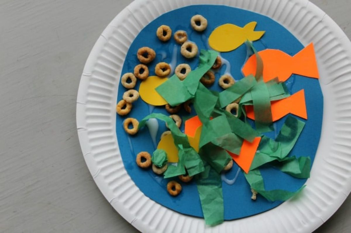 a paper plate has been decorated with paper and cereal to look like an underwater scene