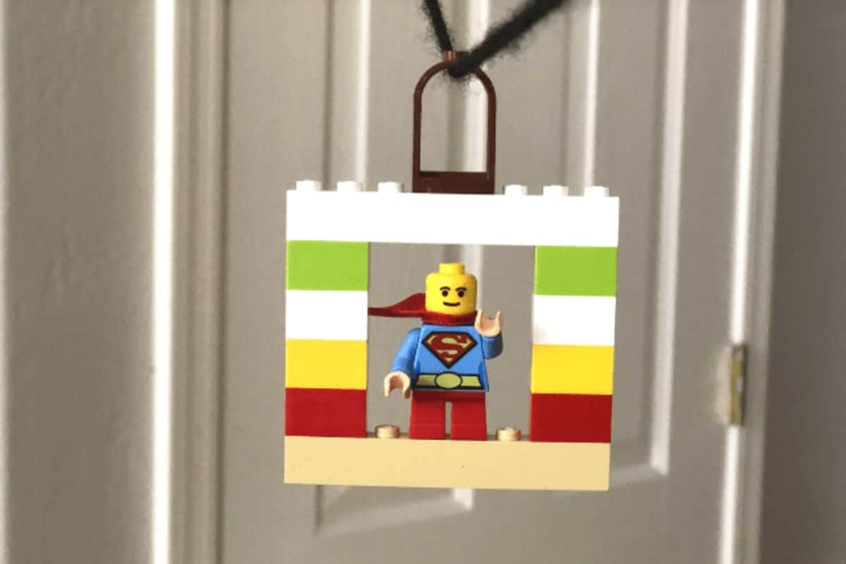 on a zip wire hangs a square of lego with a superman lego figure inside it