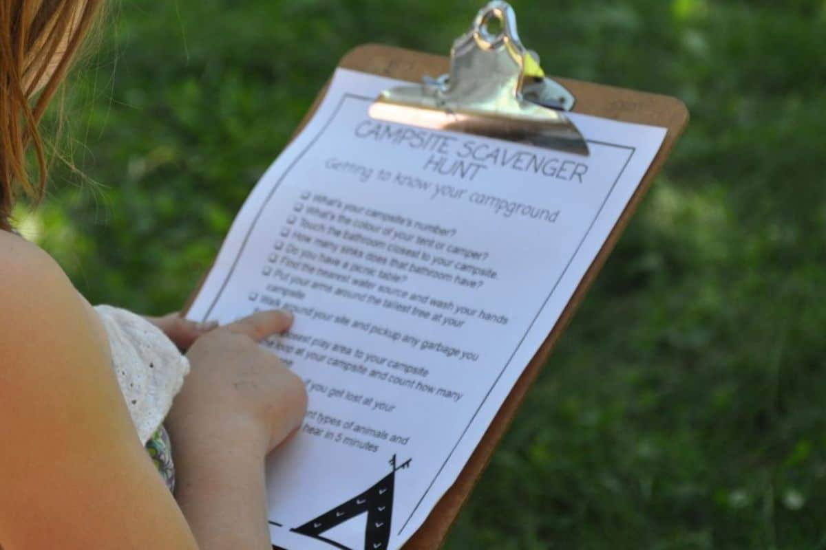A child points to a line on a scavenger hunt sheet on a clipboard.