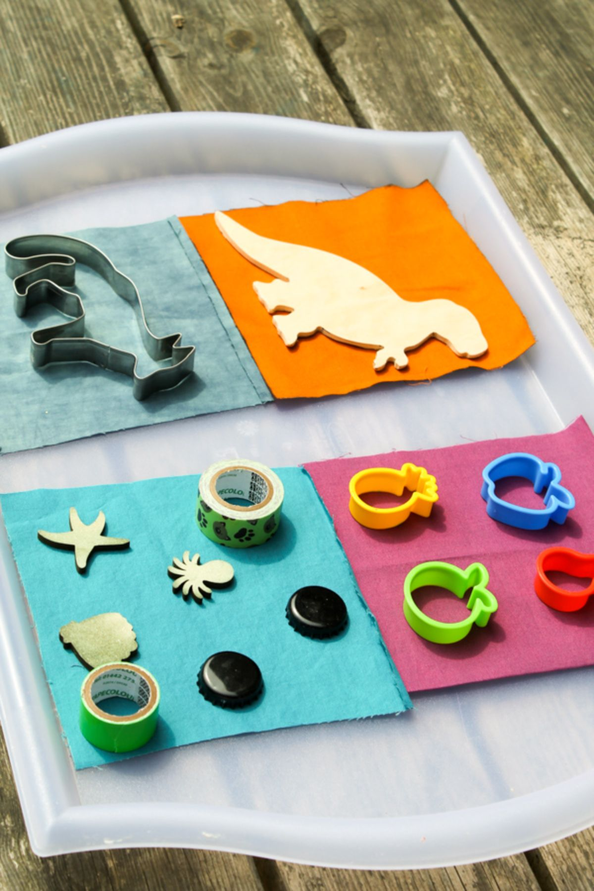 on a wooden table is a plastic tray with raised edges. 4 squares of different colored card are topped with a dinosaur cut out, a fox cookie cutter, 4 fruit shapes and some tape with 2 black bottle tops