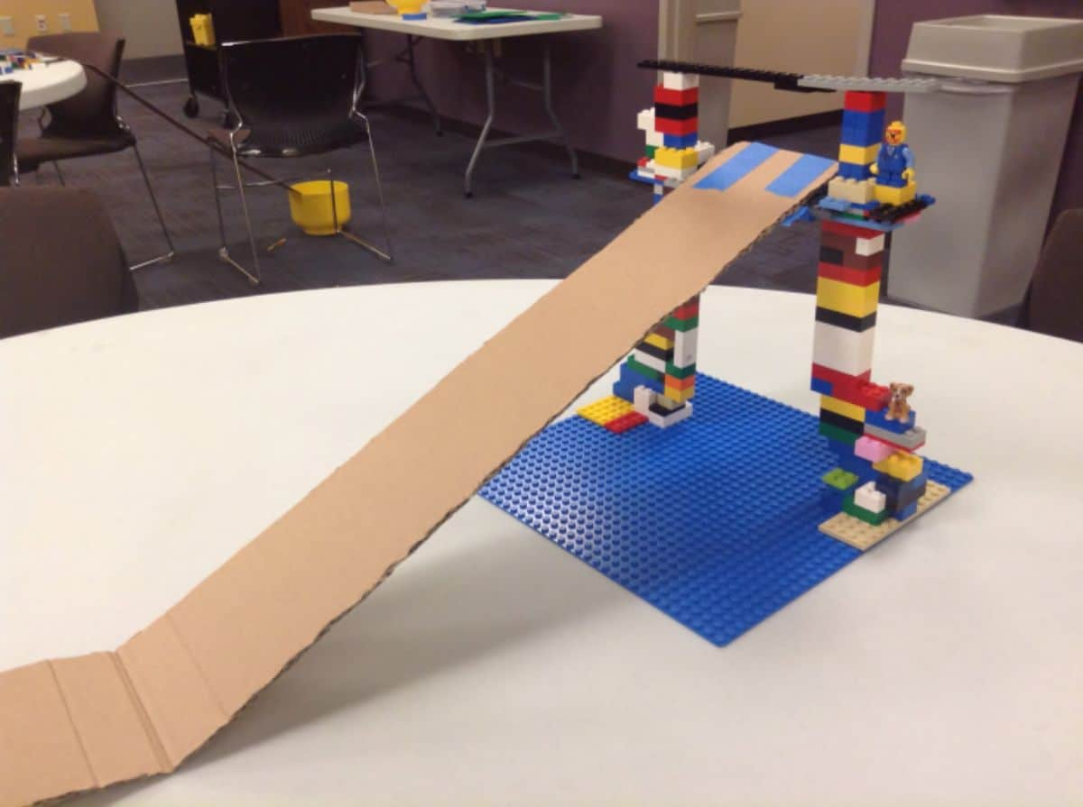 a tower made of lego sits on a table with a cardboard slide attached to it
