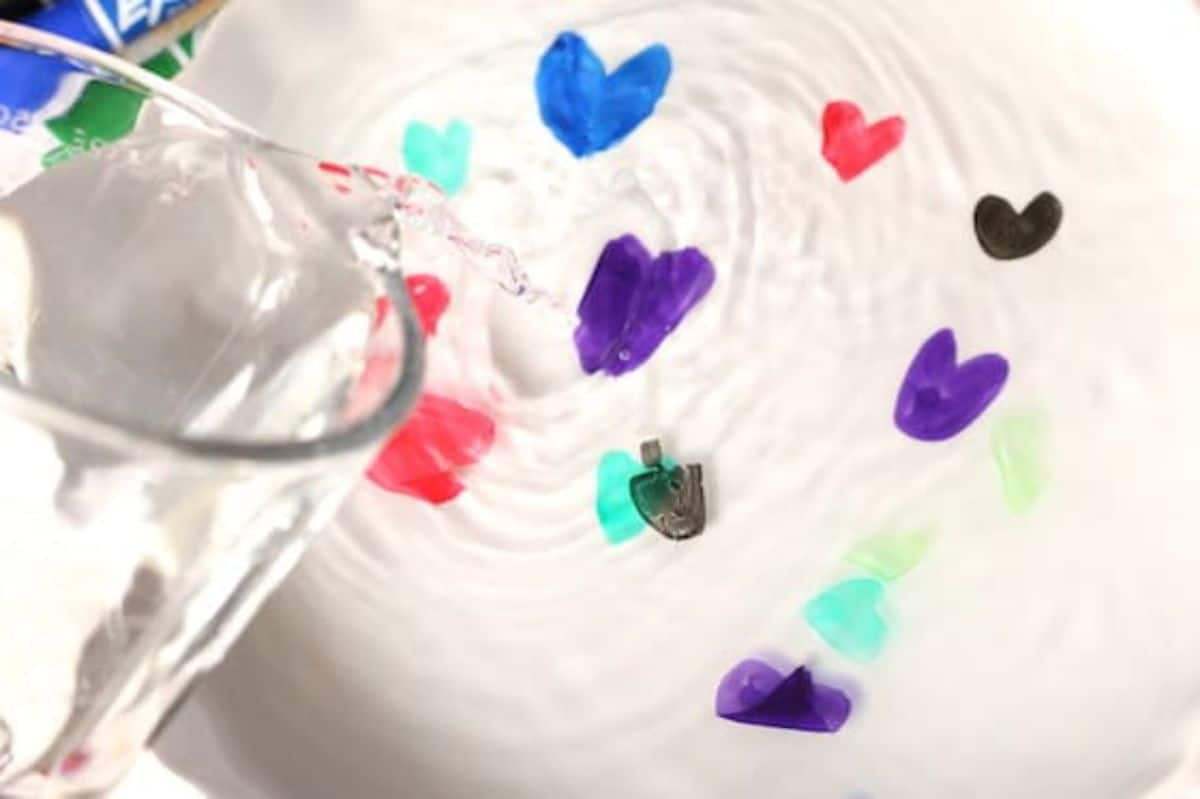 a glass jug is pouring water into a basin. coloured hearts are floating on top