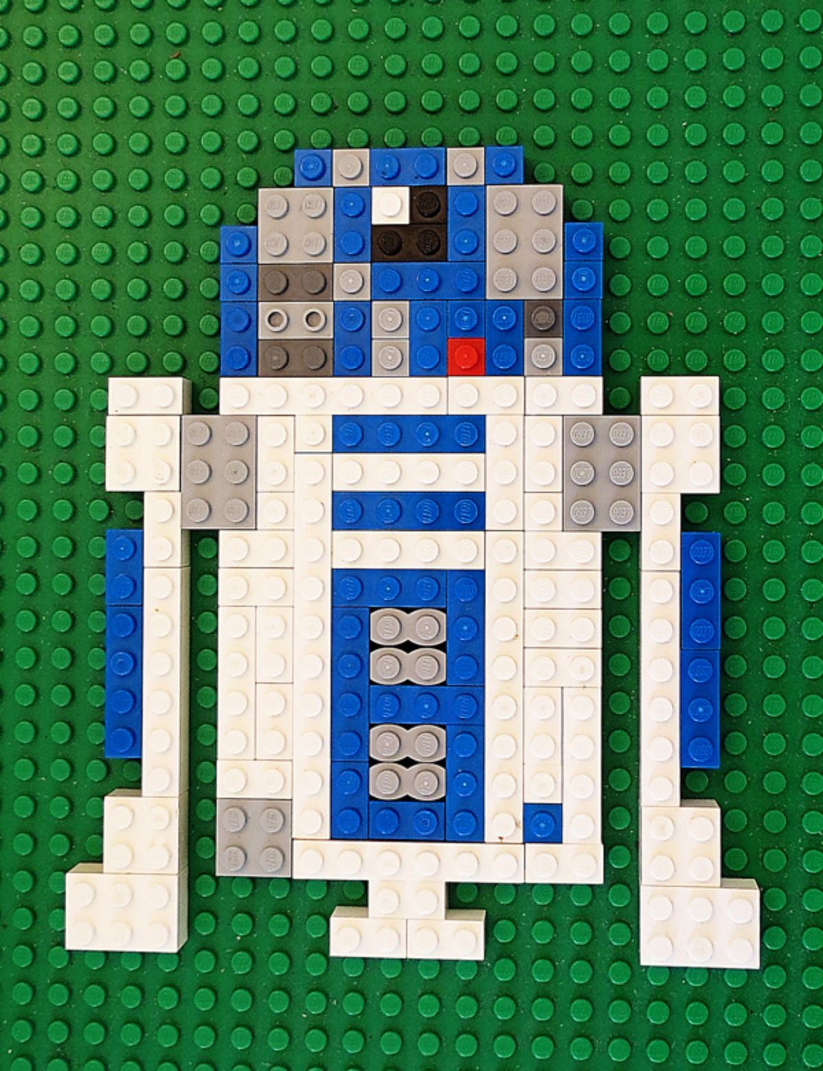 on a green lego board background is an R2D2 figure made of lego