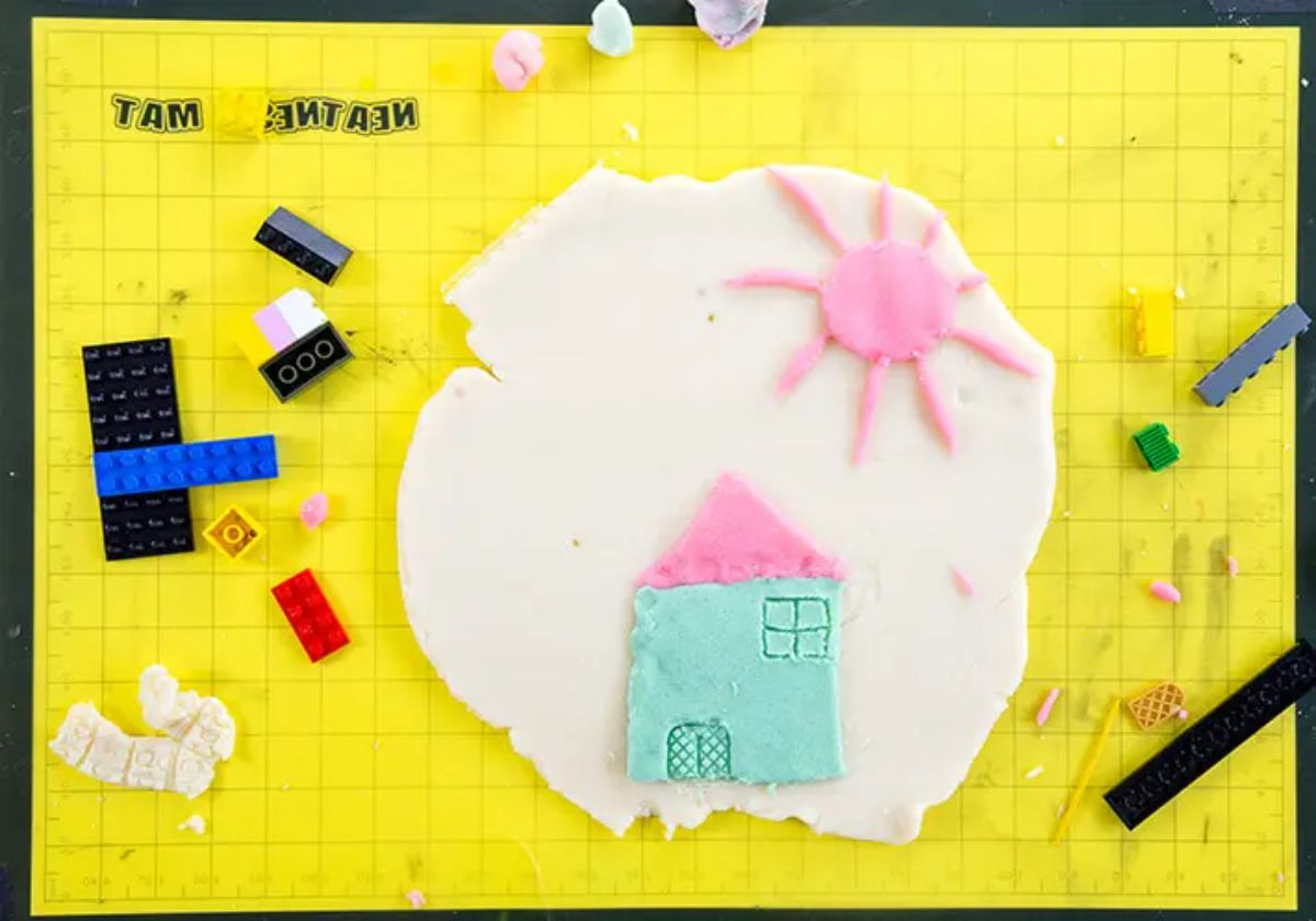on a yellow paper bacground is a picture made of playdough of a house and a sun. Scattered around are some lego bricks