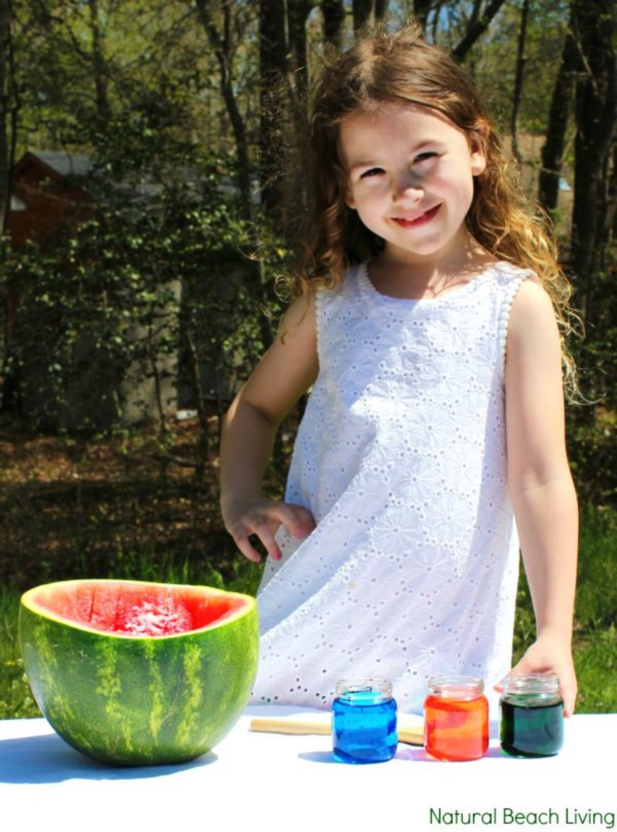 a girl in a white dress is standing in front of a table. on the table is half a watermelon hollowed out and 3 jars of coloured water