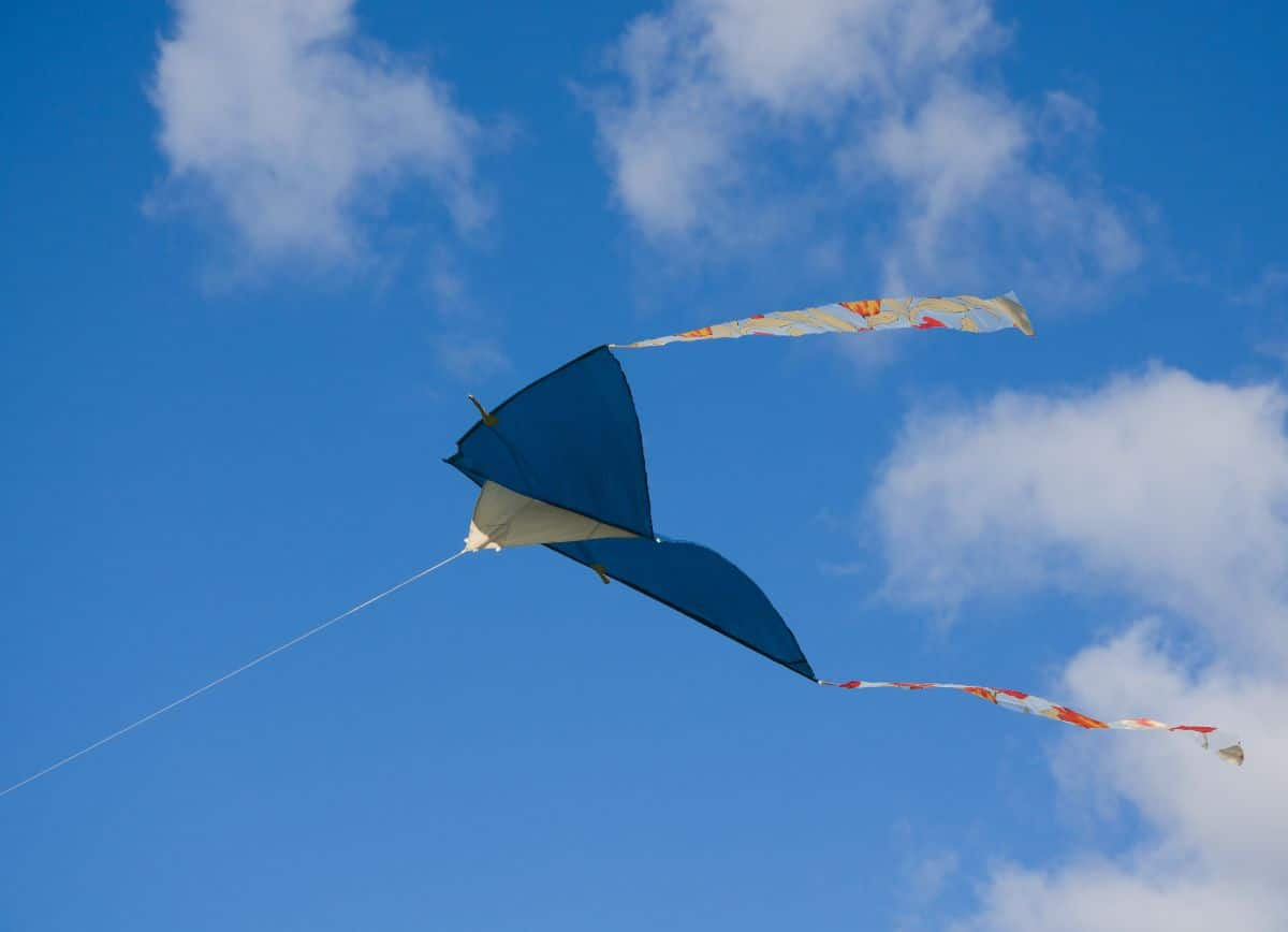 a blue kite is flying through a blue sky with a few clouds