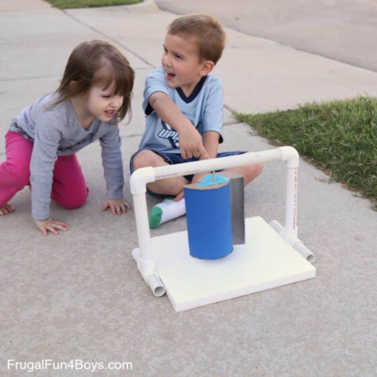 a boy and a girl are sitting on a sidewalk in front of a homemade wind turbine