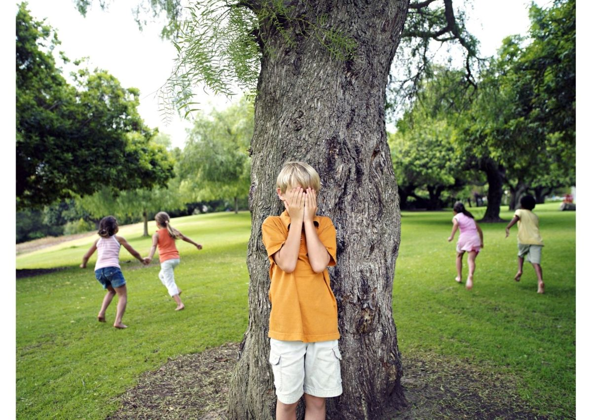 a boy in an orange shirt hides behind a tree and holds his hands over his face. 4 children run away from the boy