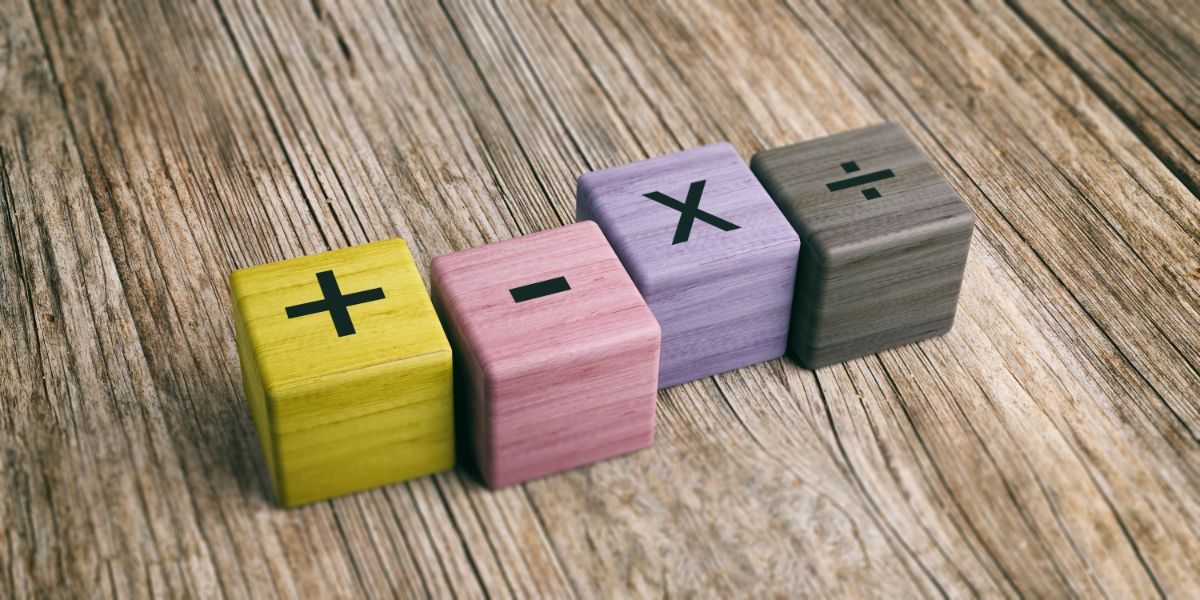a wooden table with 4 building blocks on it. The blocks are yellow pink purple and grey. They have a +, -, x, and divide signs on them