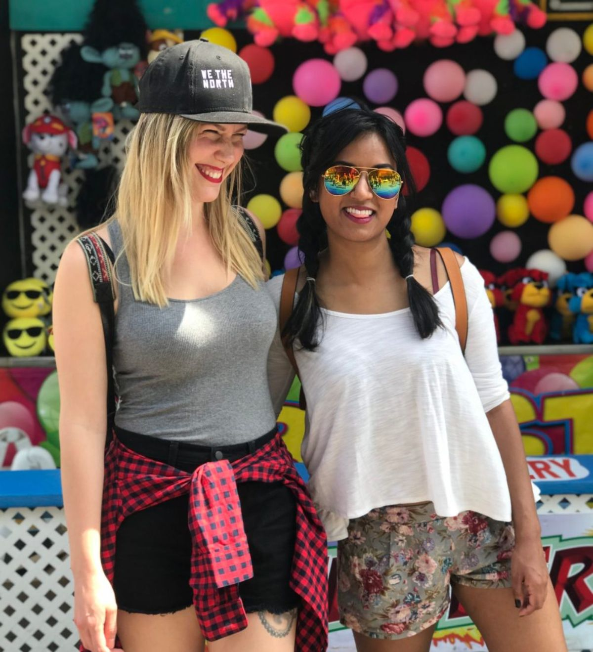 2 young women, one blonde caucasian and one brunette asian standing against a fairground stand.