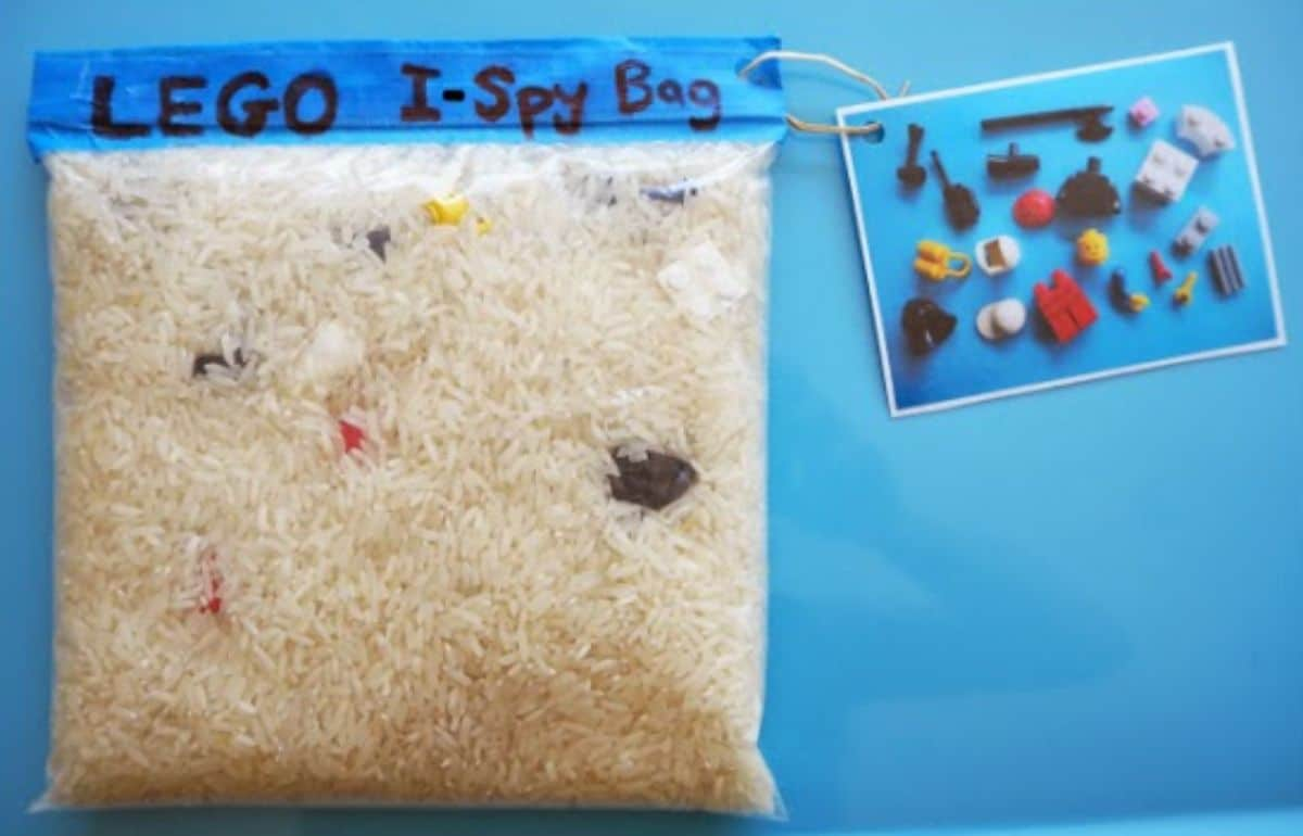 """A ziplock bag is filled with rice and lego bricks. It is labelled as """"LEGO I-Spy bag"""" and a tag with lego bricks pictured is attached to it"""