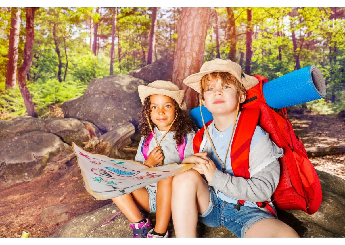 sitting on some stones in a forest are a boy and girl in straw hats, and camping equipment. They are holding a map