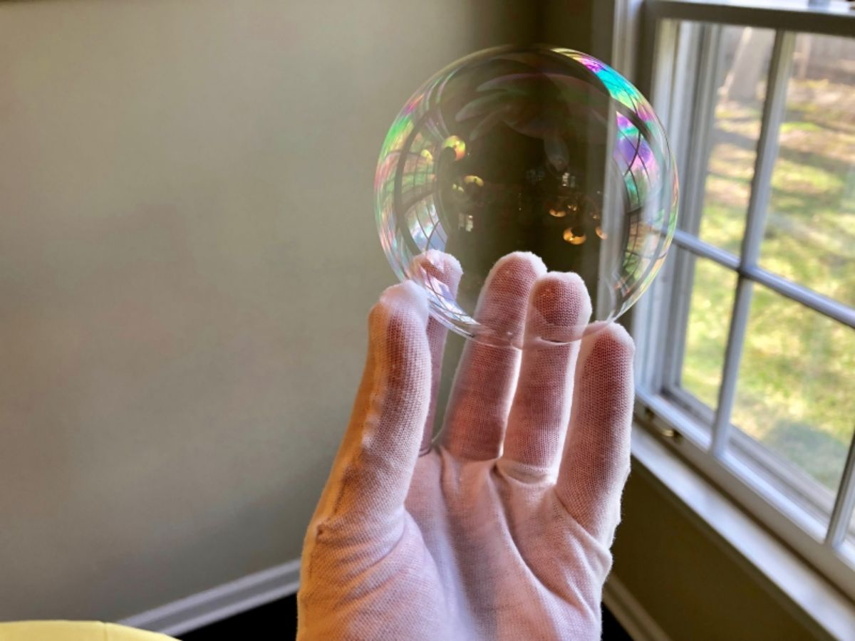 a hand in a cotton glove holds a bubble in front of a window