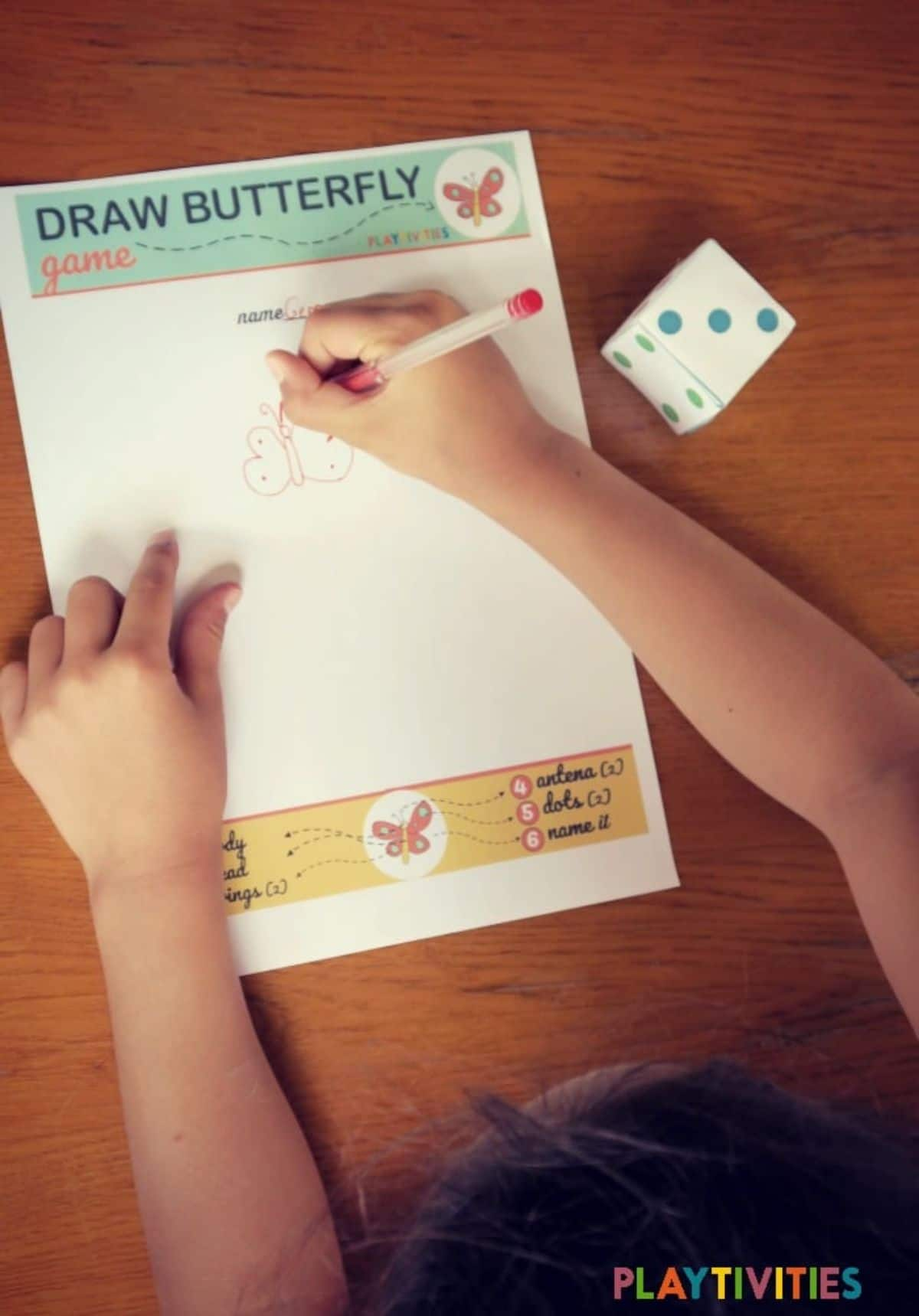 A child draws a butterfly on a piece of paper. A paper dice sits beside her