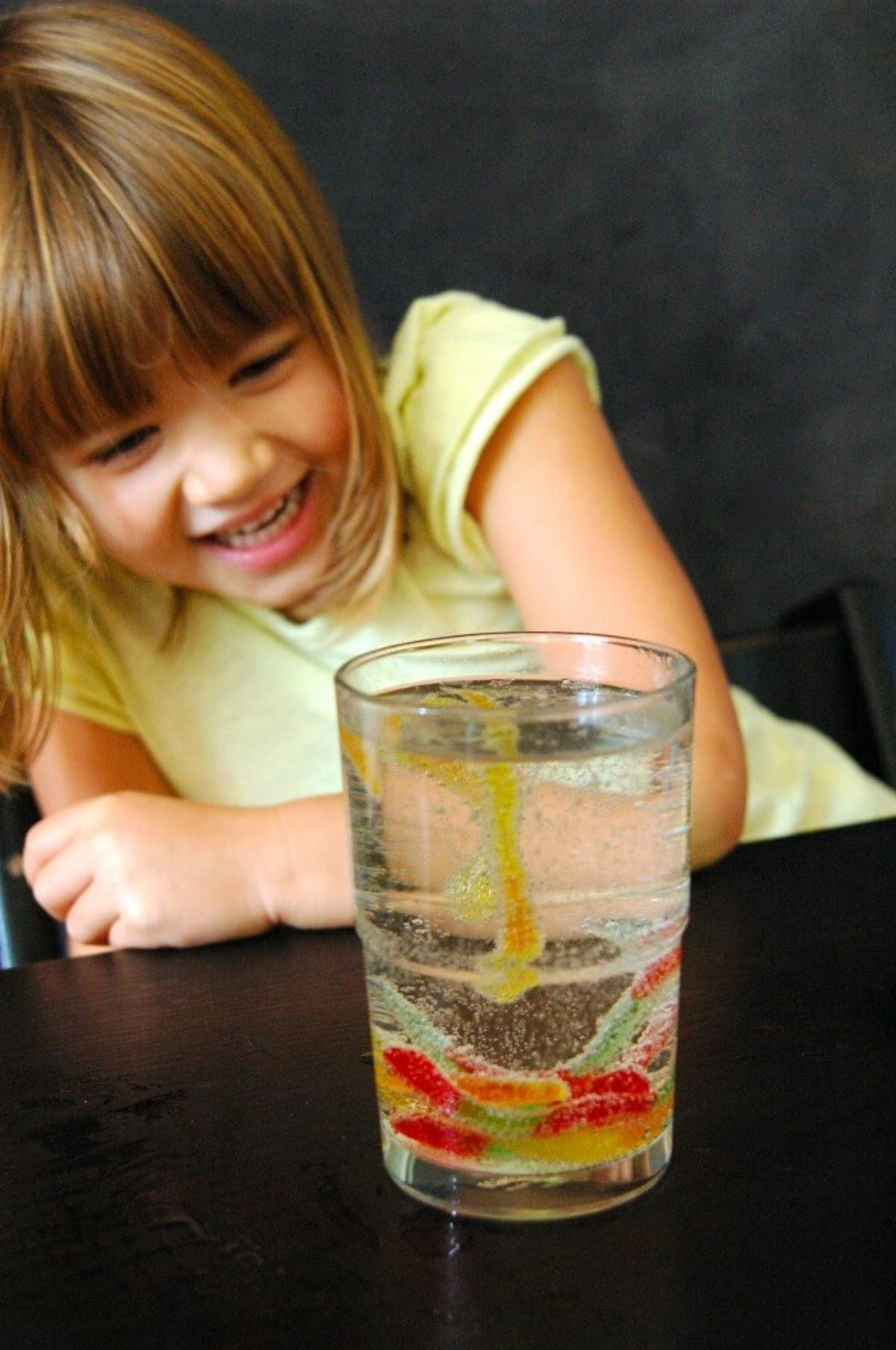 a girl in a yellow shirt sits at a table. in front of her is a glass fille dwith fizzing liquid and some jelly snake sweets