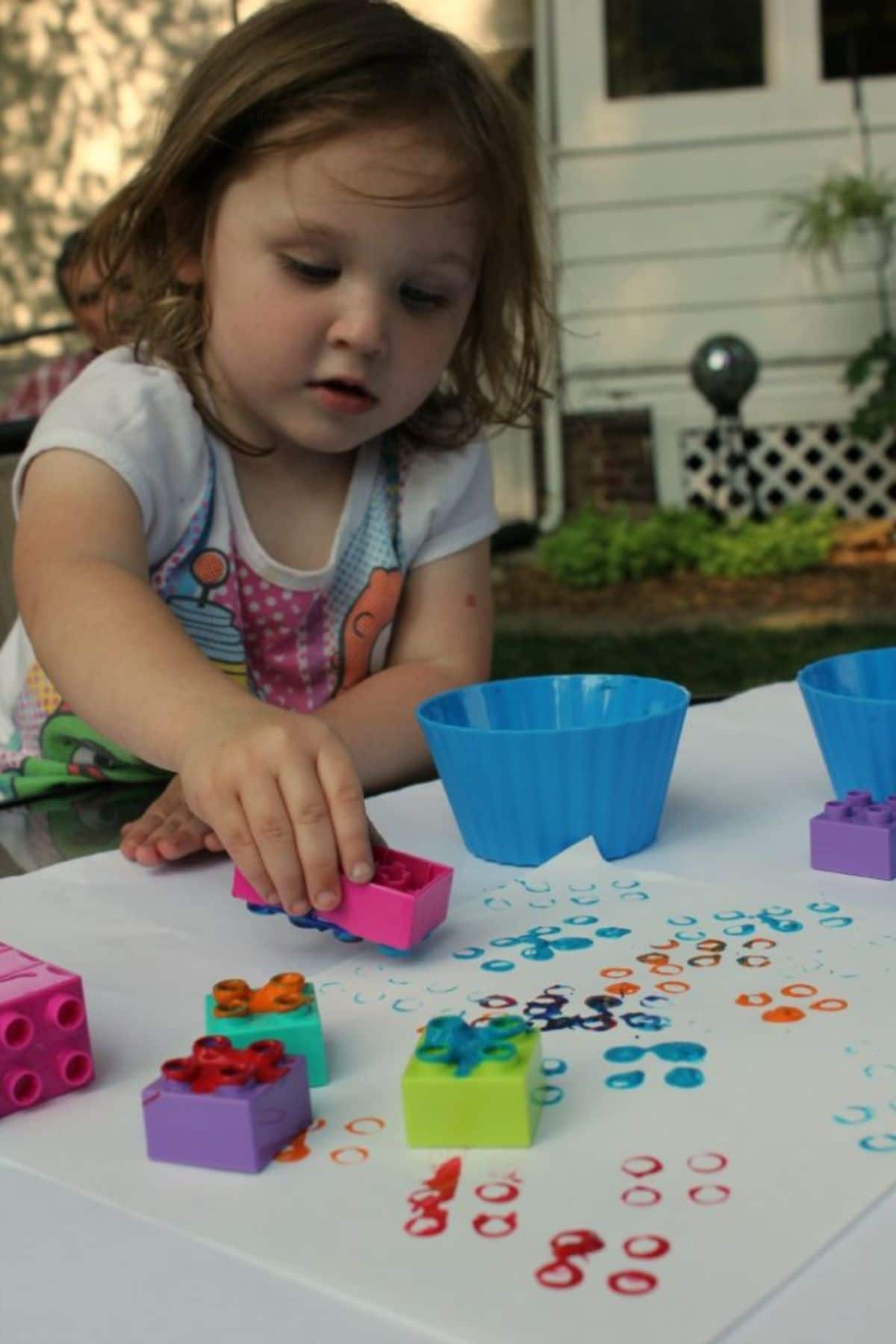 a young girl leans over a piece of paper on a table. She is printing with lego bricks dipped in paint