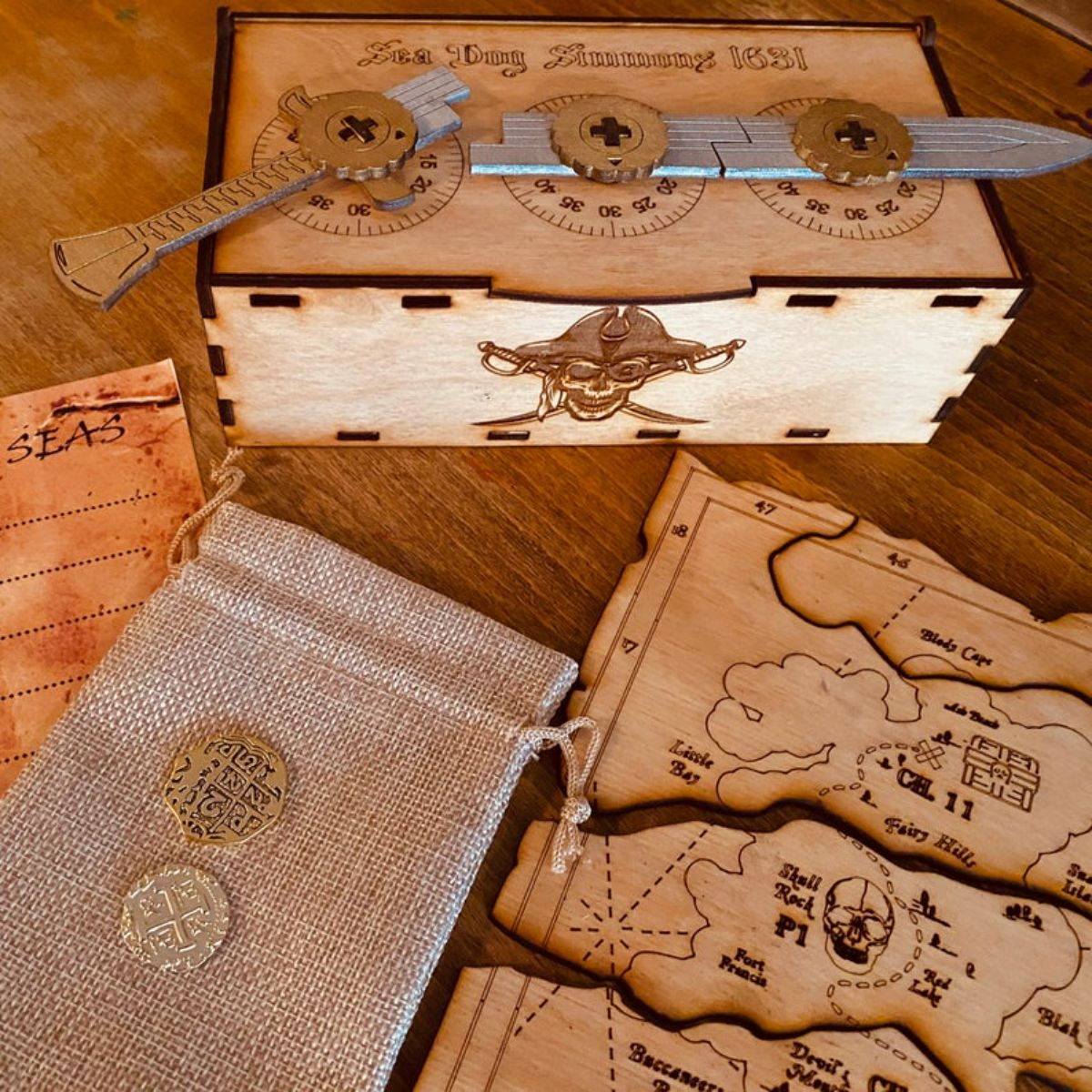 a wooden box decorated with pirate imagery and a knife lock on the top. Pirate treasure map in different pieces, and a hessian bag with 2 gold coins on top