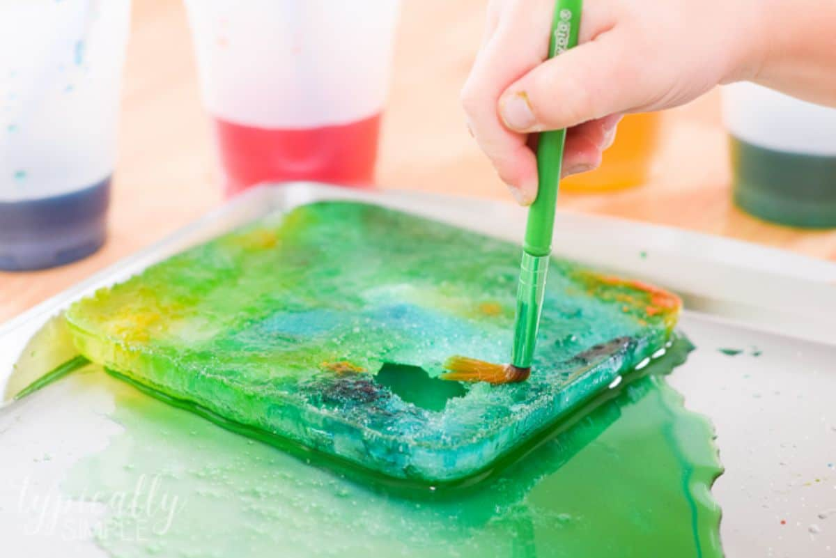 a tray of colored water with a crust. The crust is being broken by a paintbrush.