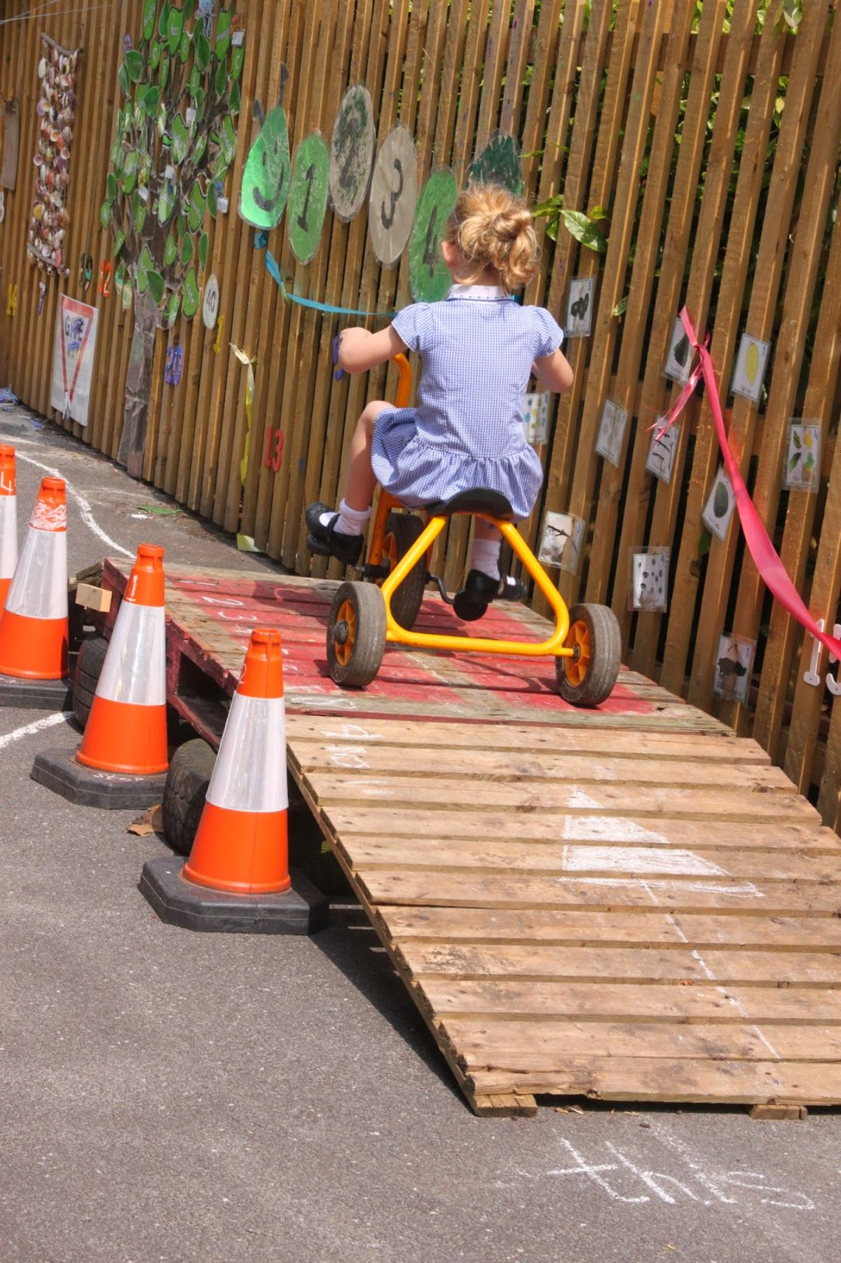 A rear view of a girl in a blue dress riding a tricyycle over a ramp made of pallets