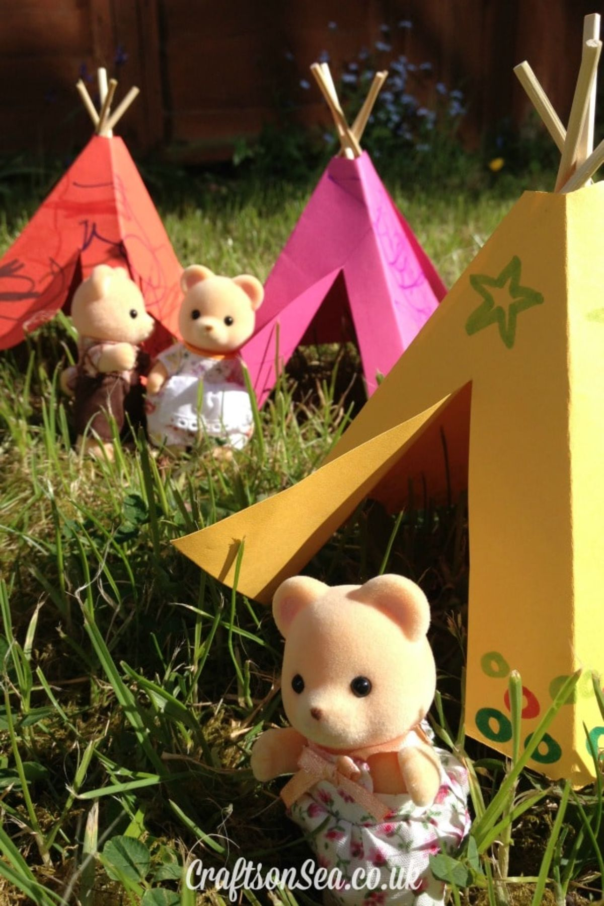 A patch of grass with 3 paper teepees on it. In front of them are 3 sylvanian family figures