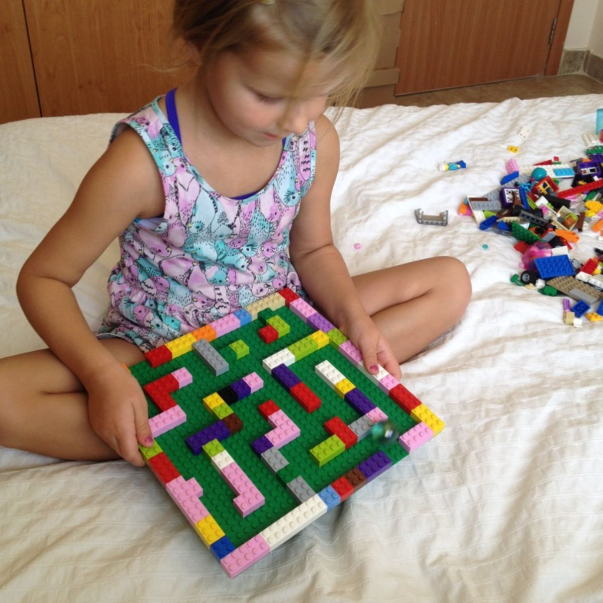 a child sits cross-legged on a bed holding a lego maze with a marble in it. a pile of lego is next to her