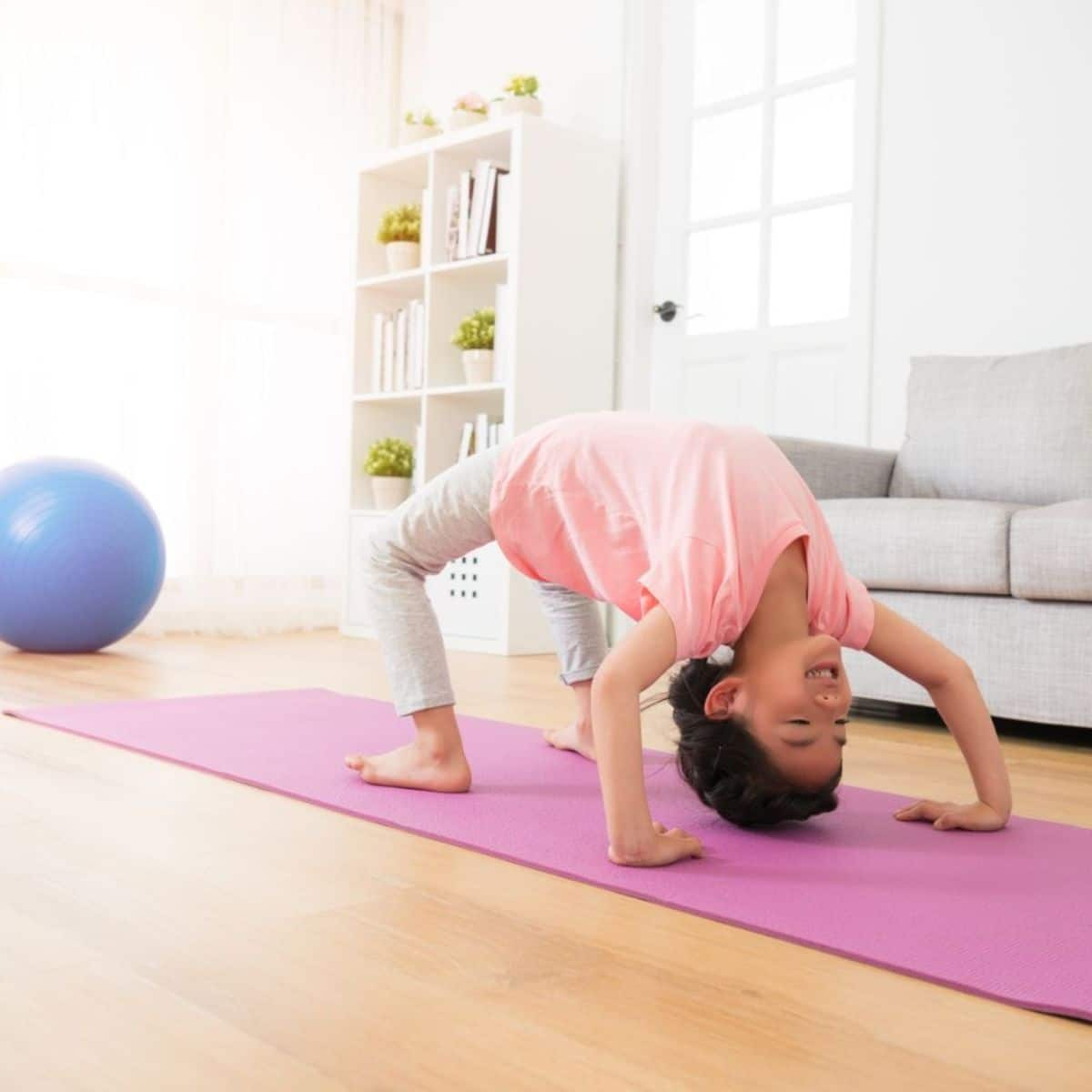 a boy in a pink shirt and trousers does a crab position on a purple yoga mat in a living room